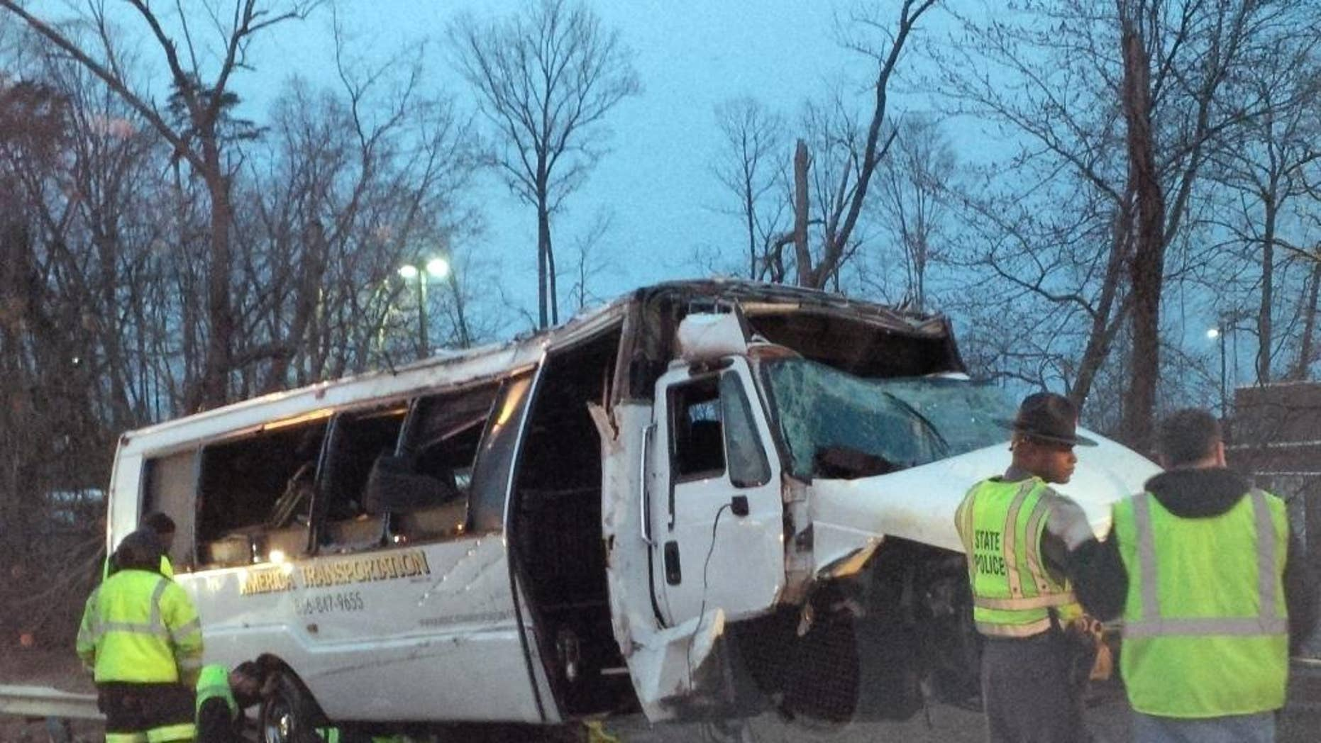 This photo provided by the Virginia State Police,  police investigate the scene of a bus accident on Interstate 95, early Sunday, March 23, 2014 in Fairfax County, Va.  The shuttle bus struck a guardrail and overturned before dawn Sunday just south of the nation's capital, leaving at least one person dead and sending 16 others to the hospital, Virginia State Police said.  The bus was headed south on the heavily traveled East Coast artery when witnesses reported a white, speeding four-door passenger vehicle swerved into the bus's travel lane. The bus then swerved to the right to avoid the sedan, ran off the road, struck the guardrail and overturned, Virginia State Police said. The crash occurred on the interstate in northern Virginia's Fairfax County and police were called at 3:28 a.m. Sunday, State Police spokeswoman Corinne Geller said. (AP Photo/Virginia State Police)
