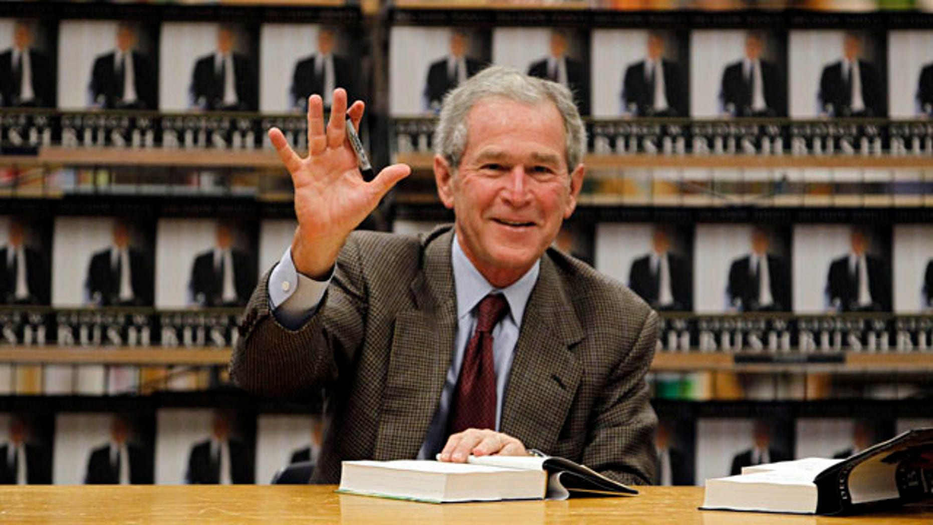 """Nov. 9: Former President George W. Bush waves as he signs copies of his book, """"Decision Points,"""" at a store near his Dallas home. In the book, Bush lists several mistakes from his years in office--referring to the condition of the economy when he exited as """"one ugly way to end a presidency."""""""