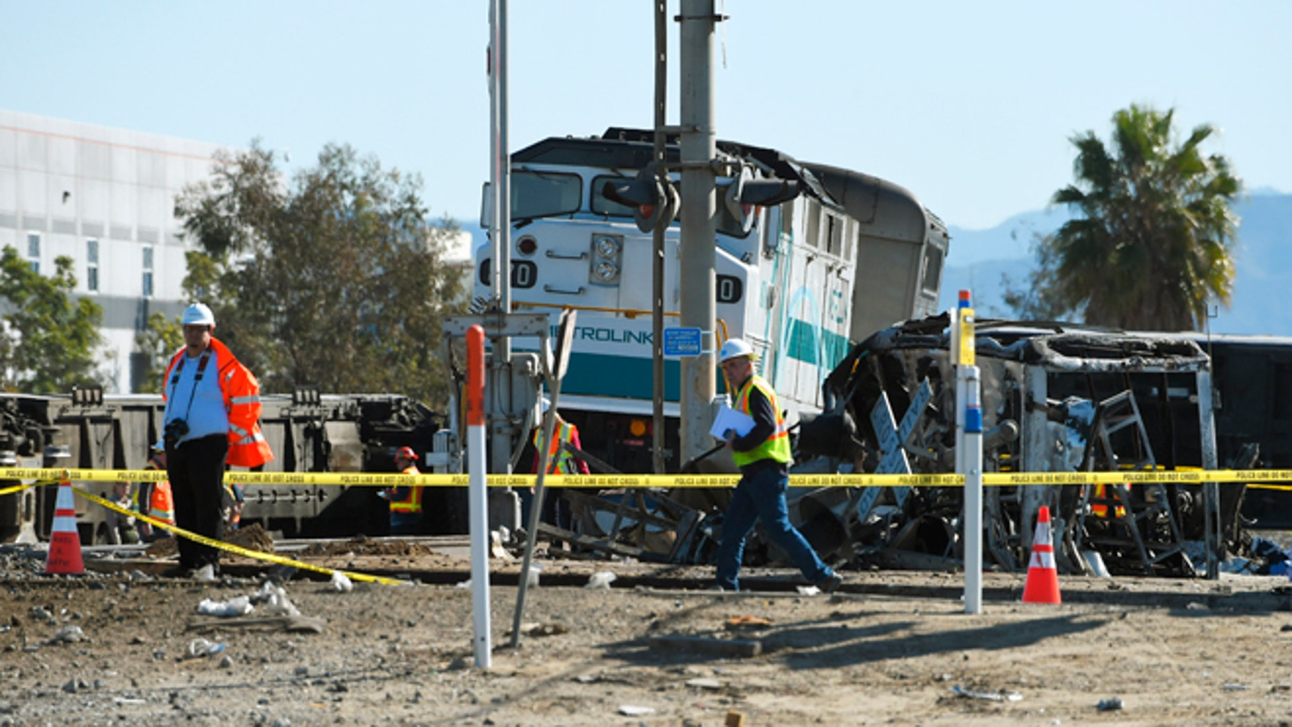 Workers walk near a Metrolink train engine from a train that hit a truck and then derailed Tuesday, Feb. 24, 2015, in Oxnard, Calif. Three cars of the Metrolink train tumbled onto their sides, injuring dozens of people in the town 65 miles northwest of Los Angeles. (AP Photo/Mark J. Terrill)
