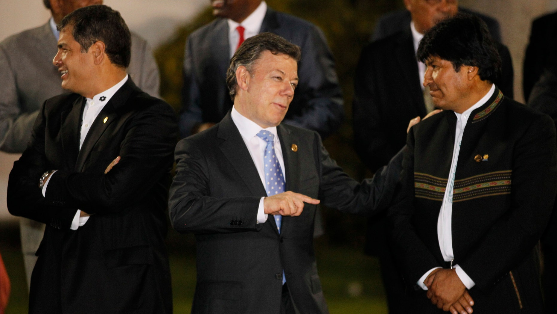 Colombia's President Juan Manuel Santos, center, talks to Bolivia's President Evo Morales as Ecuador's President Rafael Correa, left, looks on during the group photo of the Community of Latin American and Caribbean States, CELAC, summit in Caracas, Venezuela, Friday, Dec. 2, 2011. CELAC members are gathering in a two-day, 33-nation summit welcoming countries from Brazil to Jamaica, adding one more bloc to a region with other smaller organizations like Unasur, Mercosur and the Caribbean Community. (AP Photo/Ricardo Mazalan)