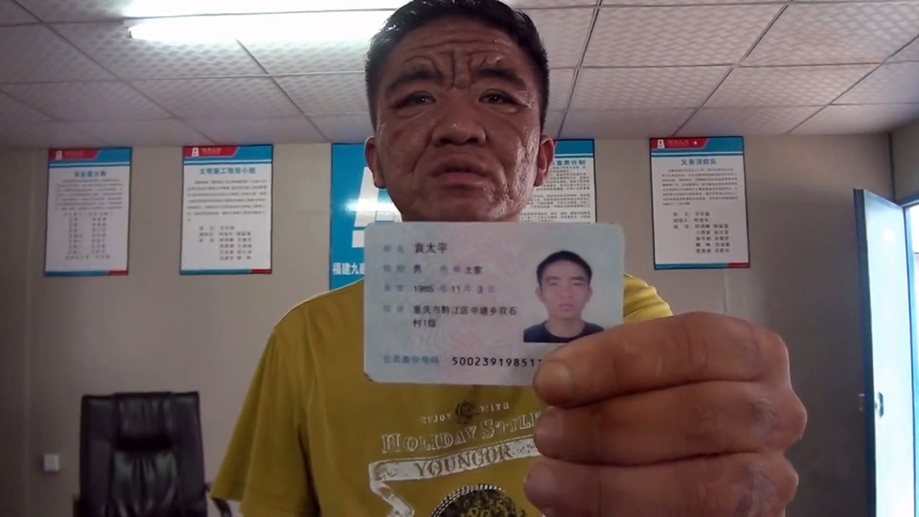 Yuan Taiping showing his ID; year of birth: 1985. (CEN)