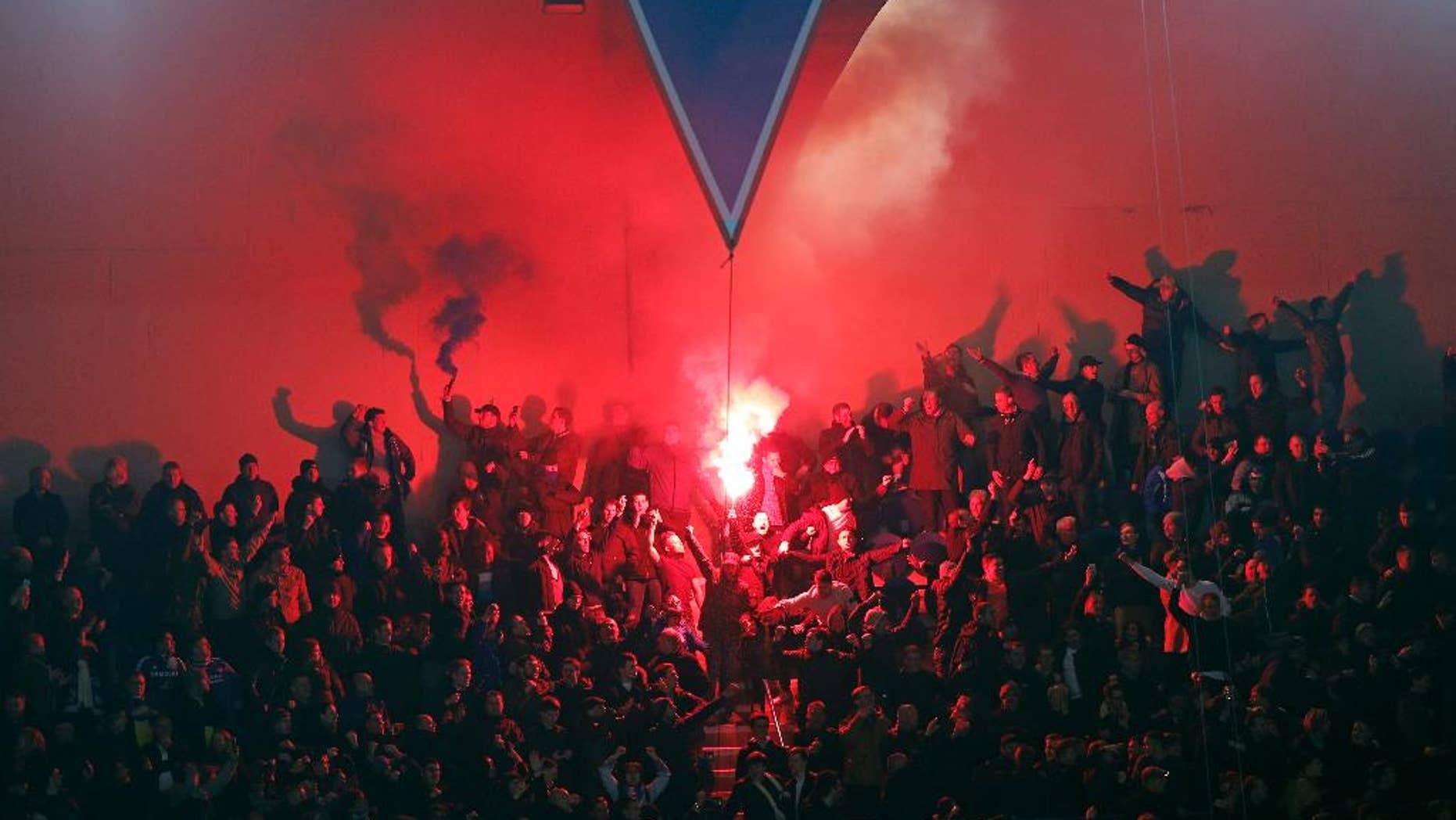 Hinchas de PSG encienden bengalas durante un partido contra Chelsea por la Liga de Campeones el martes, 17 de febrero de 2015, en París. (AP Photo/Christophe Ena)