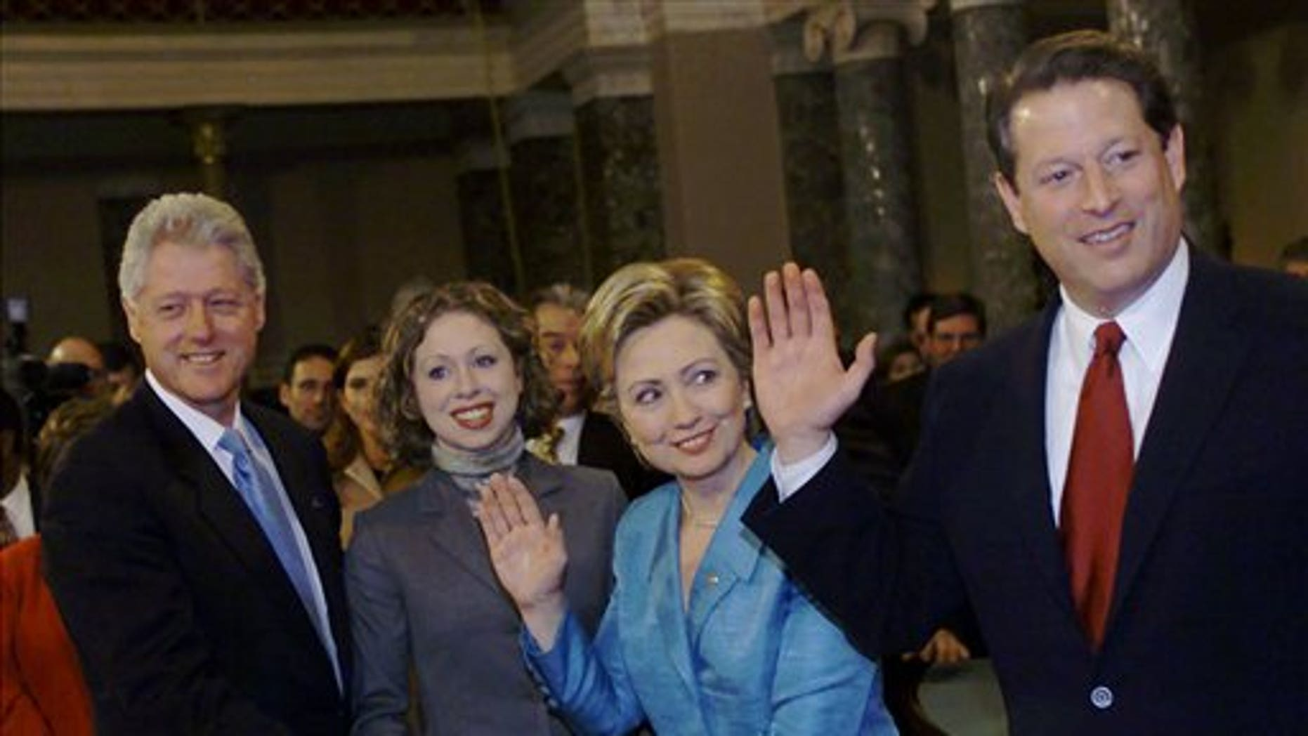 FILE - In this Jan. 3, 2001, file photo, then-President Bill Clinton, left, and daughter Chelsea hold a Bible during a mock swearing-in for freshman Sen. Hillary Rodham Clinton, D-N.Y. by Vice President Al Gore in Washington. (AP Photo/Hillery Smith Garrison, File)