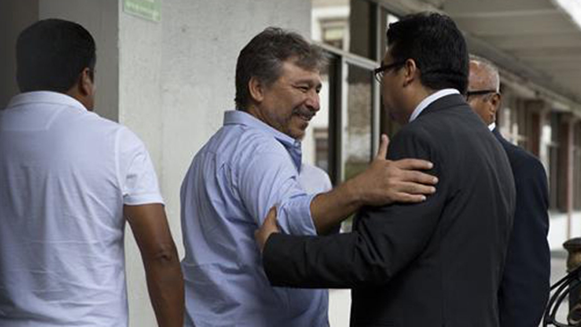 A member of a negotiation group comprised of protesting teachers and a mediation commission greets a government worker as he enters the Interior Ministry for a meeting with Secretary of the Interior Miguel Angel Osorio Chong, in Mexico City, Wednesday, June 22, 2016. The negotiations between the striking radical teachers and the government come three days after a clash between protestors and police in Oaxaca state left eight dead. Though who started shooting is disputed, journalists filmed police firing their weapons in the confrontation, which also left more than 100 injured. (AP Photo/Rebecca Blackwell)