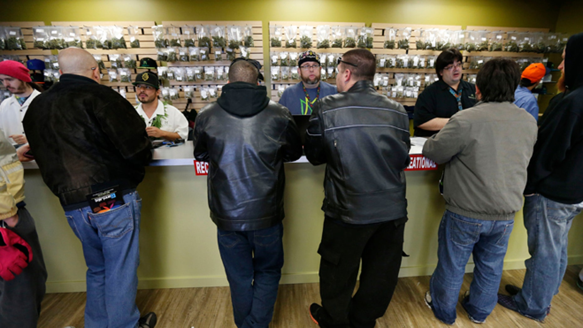 """Employees help customers at the crowded sales counter inside Medicine Man marijuana retail store, which opened as a legal recreational retail outlet in Denver on Wednesday Jan. 1, 2014. Colorado began retail marijuana sales on Jan. 1, a day some are calling """"Green Wednesday."""" (AP Photo/Brennan Linsley)"""