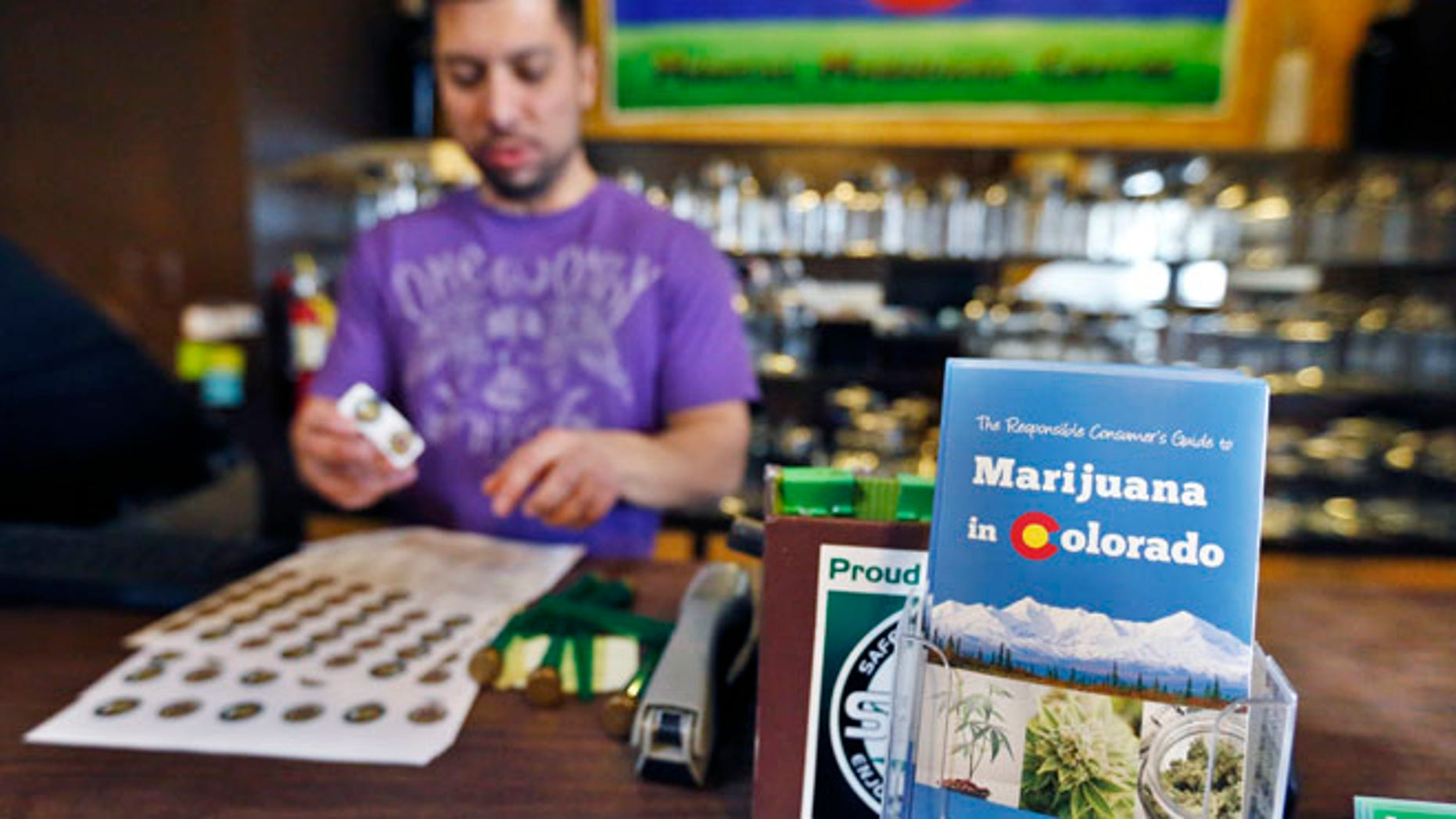 General manager David Martinez labels containers of retail marijuana, behind a sales bar fitted with a brochure available to customers, at 3D Cannabis Center in Denver, Dec. 31, 2013.