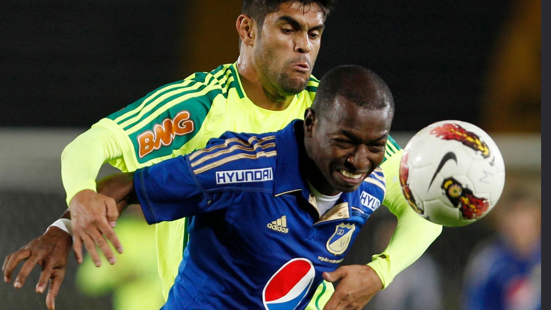 Brazil's Palmeriras' Obina, back, and Colombia's Millonarios' Wason Renteria struggle for the ball during a Copa Sudamericana soccer match in Bogota, Colombia, Tuesday, Oct. 23, 2012. (AP Photo/Fernando Vergara)