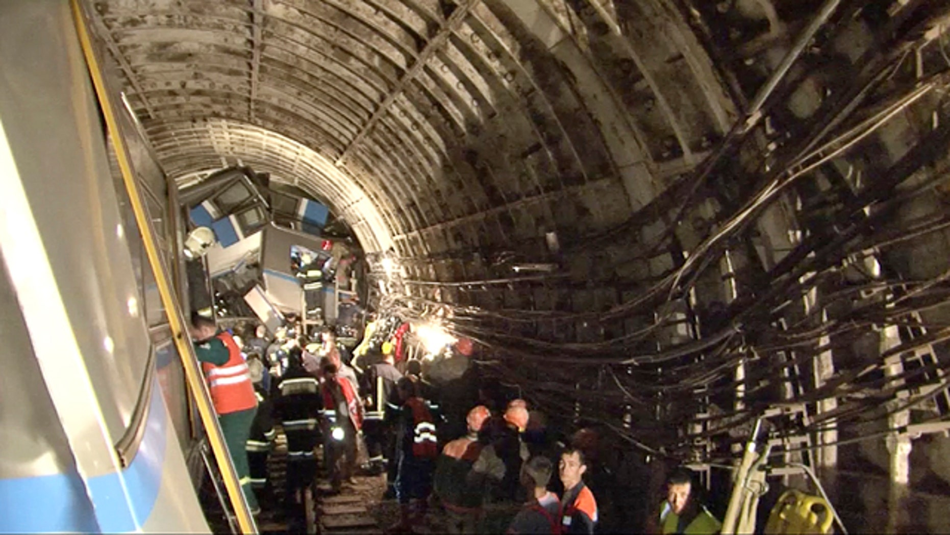 July 15, 2014: This frame grab from a video provided by the Russian Ministry for Emergency Situations shows rescue teams working inside the tunnel where several cars of a wrecked Moscow subway train are located. (AP Photo/Russian Emergency Situation Ministry)