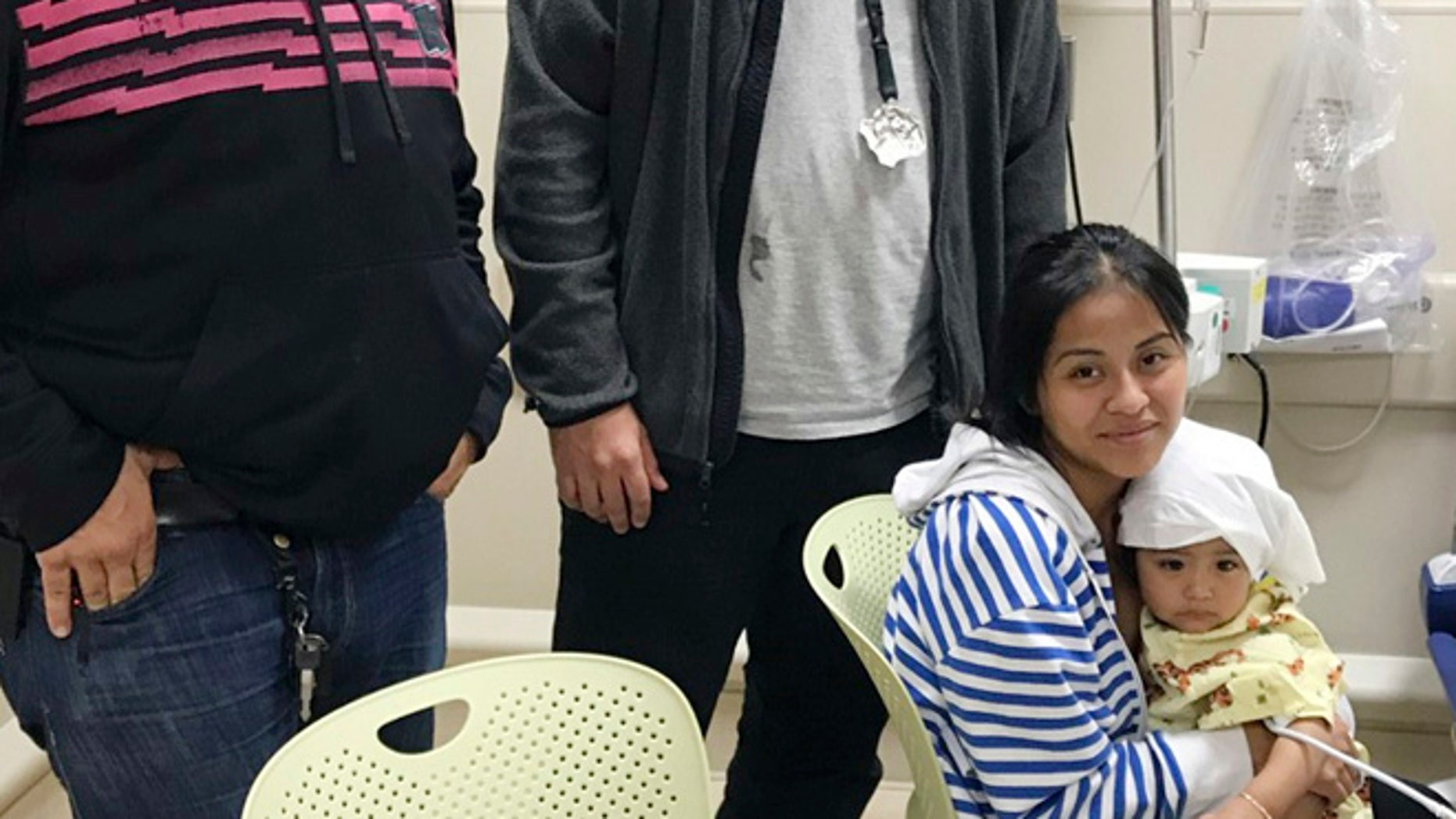 In this Oct. 14, 2016 photo released by the New York City Police Department, officers Felix Baez, left, and Giovanni Laguna pose for a photo with Lilina Benigno, and her one-year-old baby Ashley Dolores, at Lincoln Hospital in The Bronx borough of New York.  (New York City Police Department via AP)