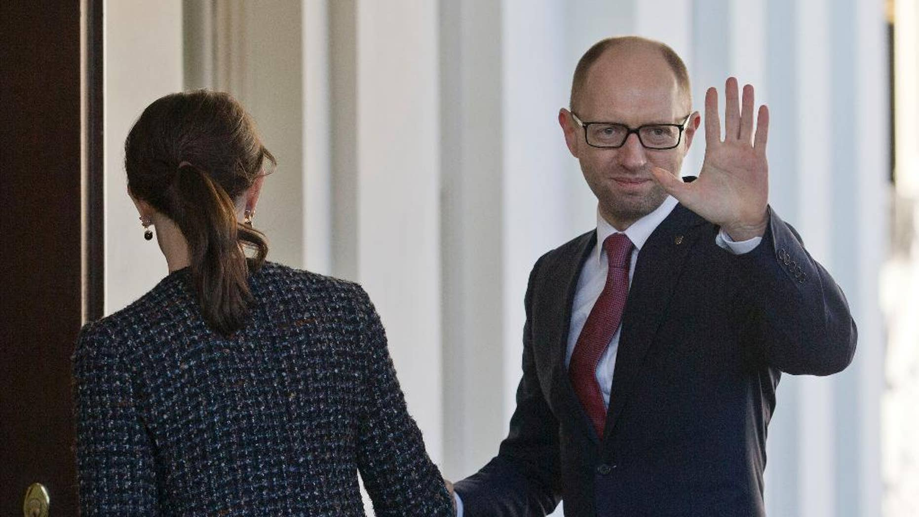 CORRECTS PHOTOGRAPHER TO PABLO MARTINEZ MONSIVAIS Ukraine Prime Minister Arseniy, right, waves as he is greeted by US acting Chief of Protocol Natalie Jones, left, during his arrival at the White House in Washington, Thursday, March 13, 2014. Arseniy is meeting with Vice President Joe Biden before traveling to New York to visit the United Nations. (AP Photo/Pablo Martinez Monsivais)