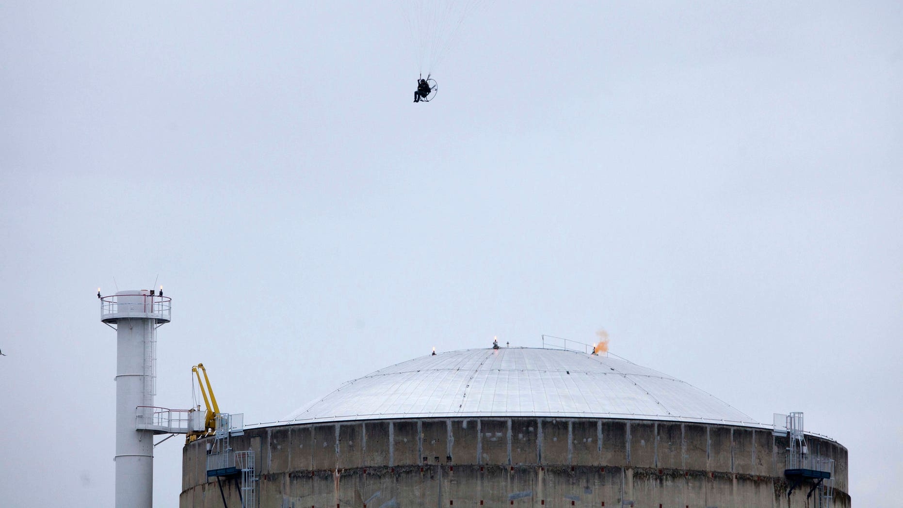 May 2, 2012: In this photo provided by Greenpeace, an activist in a motorized paraglider flies over the Bugey nuclear power plant, near Saint-Vulbas, central France, and drops a flare on the roof.