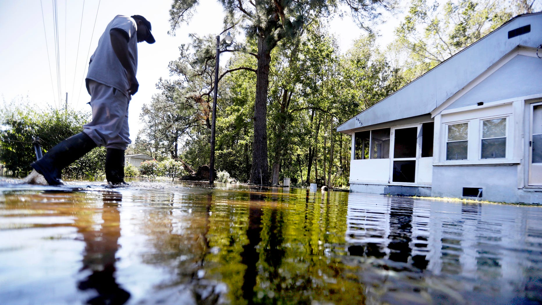 CORRECTS TO EDISTO ISLAND SOUTH CAROLINA, NOT GEORGIA - Kyle Simmons wades through water to check on the home of his grandmother following Hurricane Matthew in Edisto Island, S.C., Sunday, Oct. 9, 2016. A deteriorating Matthew was stripped of hurricane status Sunday morning and began making its slow exit to the sea. (AP Photo/David Goldman)