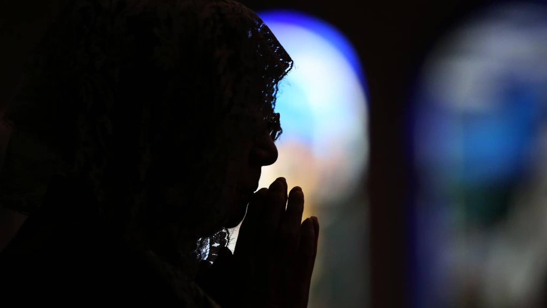 CORRECTS THE NUMBER OF THE VICTIMS- A Catholic offers prayers at an early morning mass to pay respect to the victims of the Nagasaki atomic bombing at the Urakami Cathedral in Nagasaki, southern Japan Sunday, Aug. 9, 2015. Ceremony for the 70th anniversary of the atomic bombing will start late this morning. The atomic bomb attack on this city that left more than 70,000 dead and hastened the end of World War II exactly 70 years ago.(AP Photo/Eugene Hoshiko)