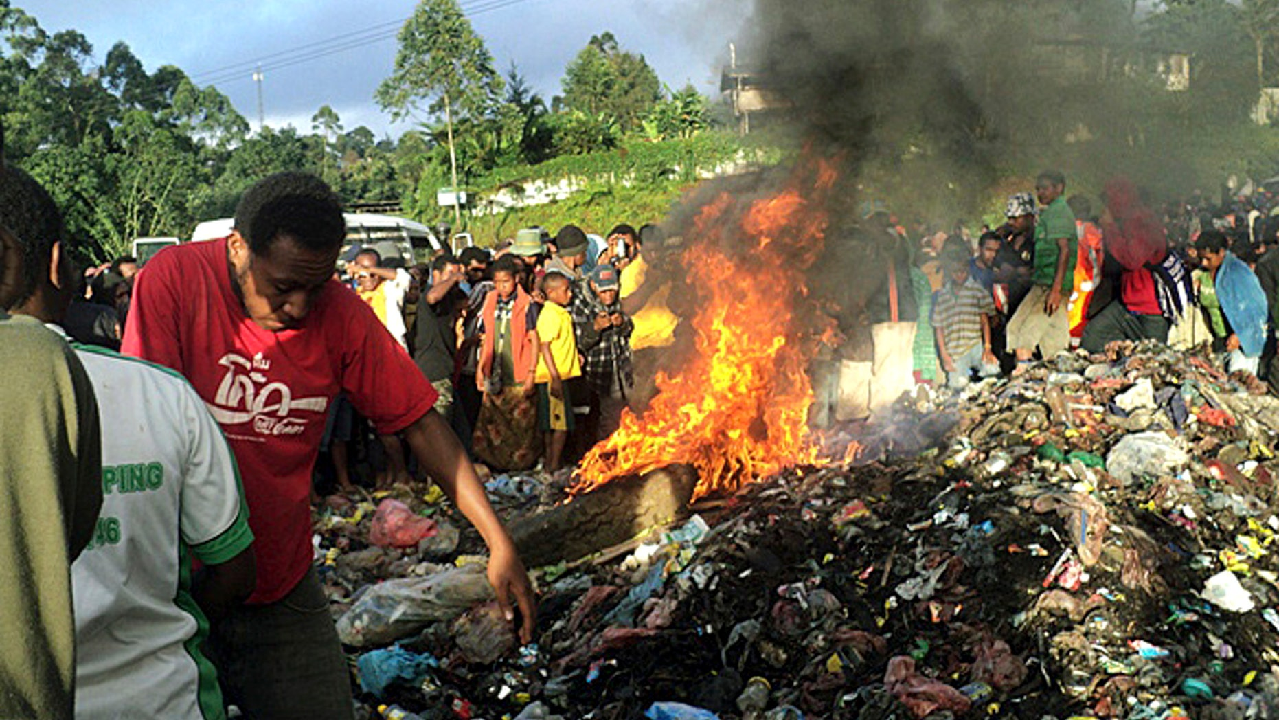 Feb. 6, 2013 - FILE photo: Hundreds of bystanders watch Kepari Leniata, a woman accused of witchcraft, being burned alive in the Western Highlands provincial capital of Mount Hagen in Papua New Guinea. There is no clear explanation for the apparent uptick in killings in parts of the South Pacific nation, and even government officials seem at a loss to say why this is happening. Some argue recent violence is fueled not by the nation's widespread belief in black magic but instead by economic jealousy.