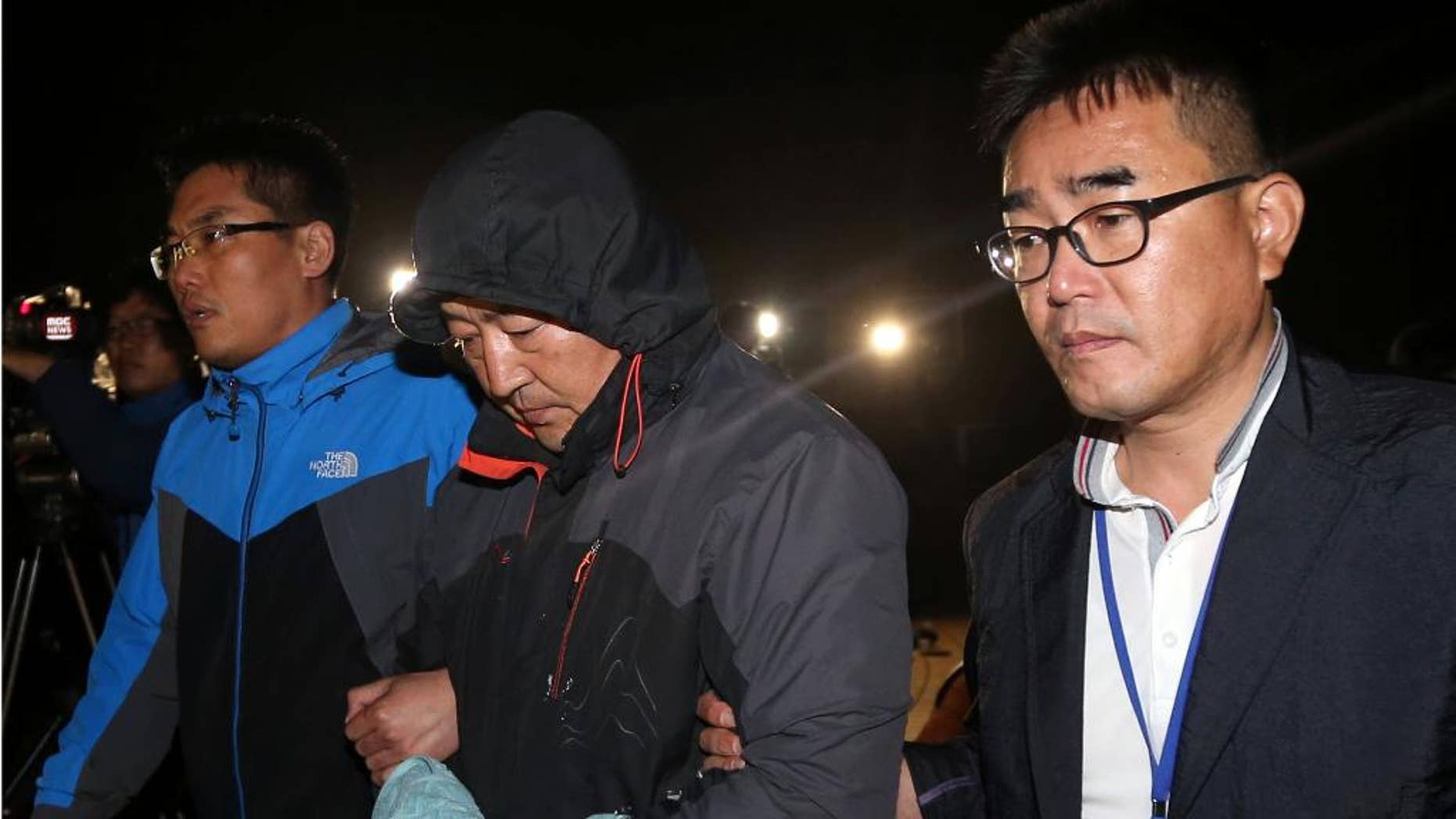 CORRECTS ID TO CREW MEMBER FROM CAPTAIN - Oh Yong-suck, center, a crew member of the sunken ferry Sewol in the water off the southern coast, leaves a court which issued his arrest warrant in Mokpo, south of Seoul, South Korea, Saturday, April 19, 2014. The investigation into South Korea's ferry disaster focused on the sharp turn it took just before it began listing and on the possibility that a quicker evacuation order by the captain could have saved lives, officials said Friday, as rescuers struggled to find some 270 people still missing and feared dead. (AP Photo/Yonhap) KOREA OUT
