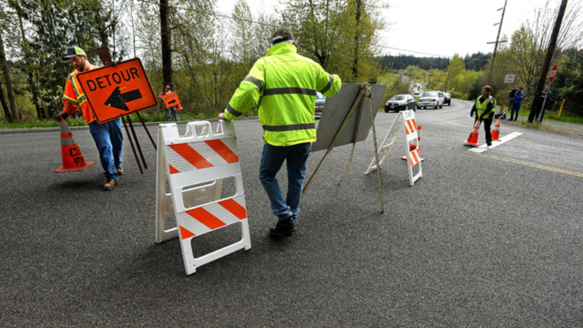 April 13, 2015: Workers with the Bonney Lake Public Works Department set up signs along Sumner-Buckley Highway to divert traffic away from Angeline Road East in Bonney Lake, Wash., after three people were killed when a piece of concrete fell from an overpass onto a pickup truck in the roadway below. (David Montesino/The News Tribune via AP)