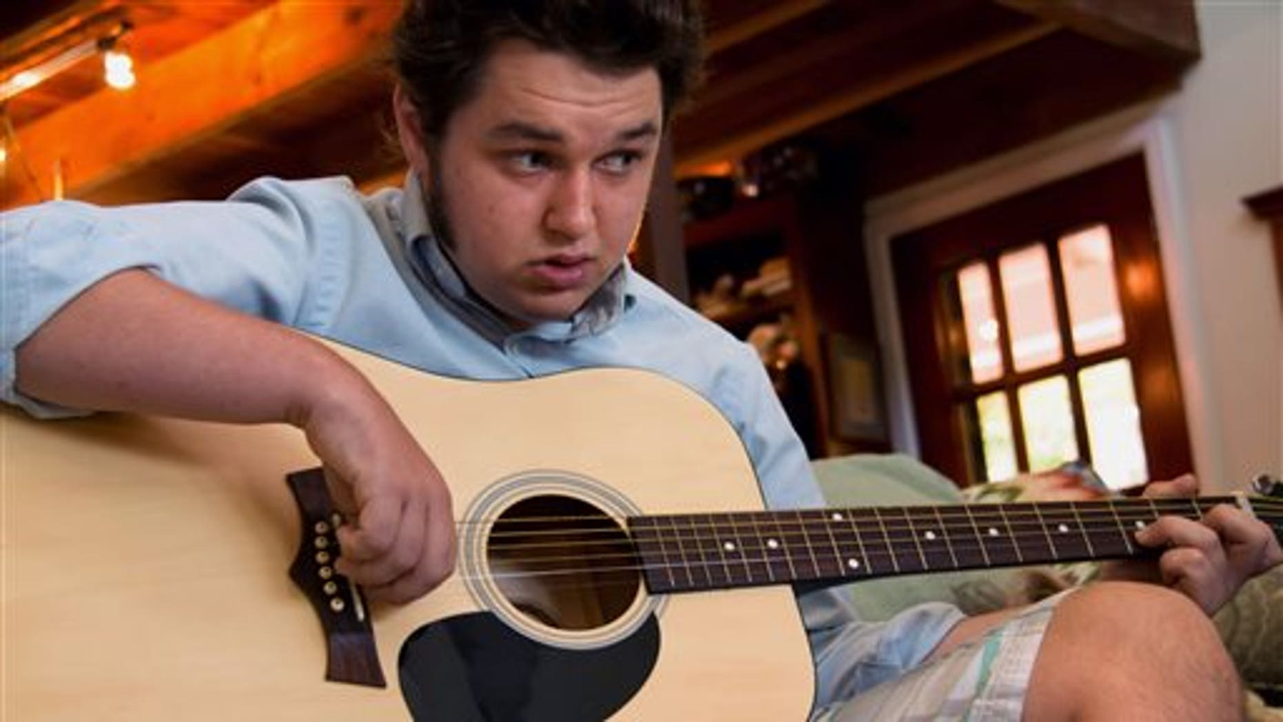 Oct. 24, 2014: In this photo, Jeffrey McCord, who suffered from violent and unexplained seizures as a baby, demonstrates his guitar at home in St. John, Virgin Islands. (AP)