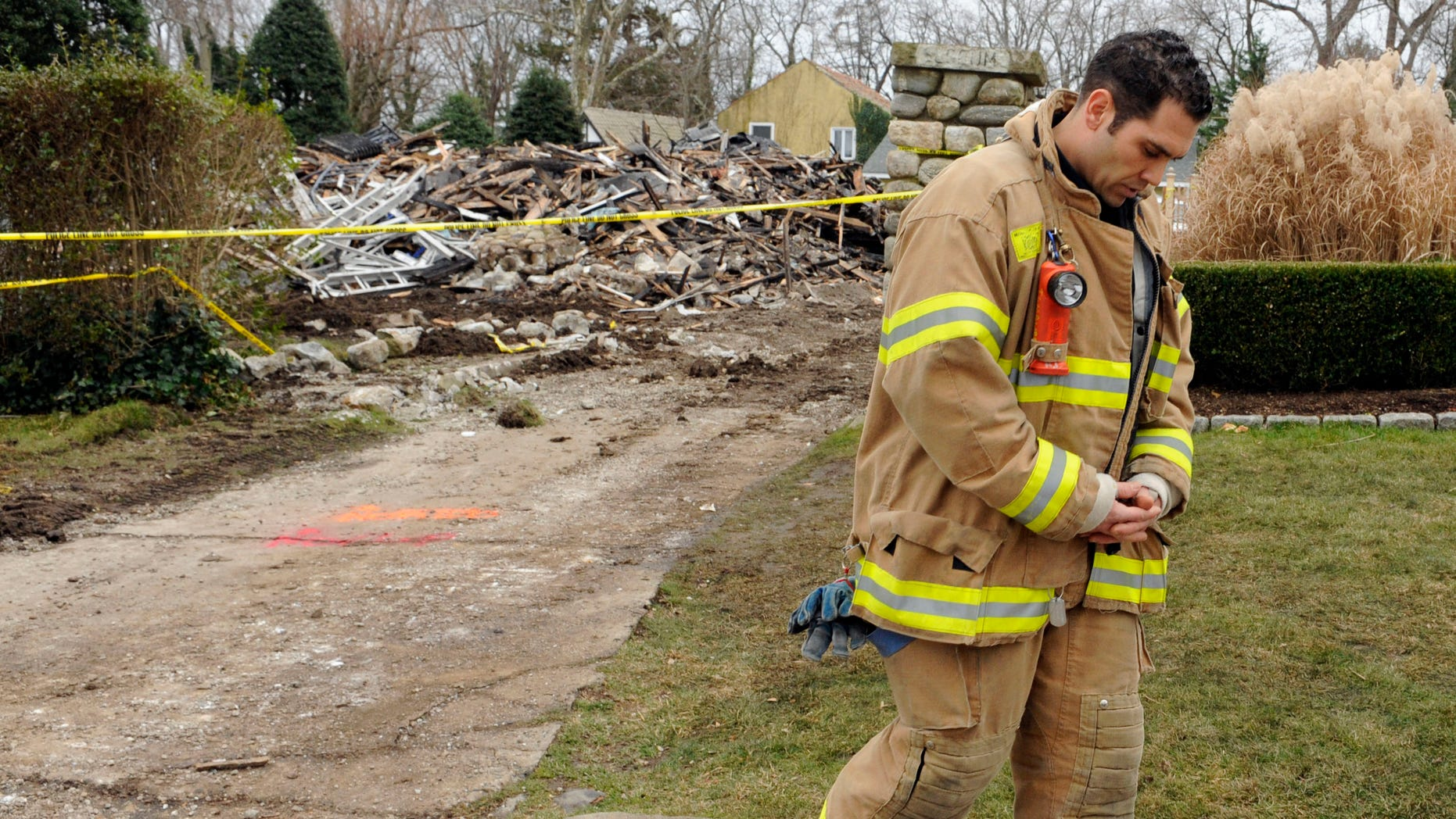 December 27: Stamford firefighter Nick Tamburro pays respect outside the home of Madonna Badger in Stamford, Connecticut. A fire at the home on Christmas morning killed Badger's three daughters and parents.