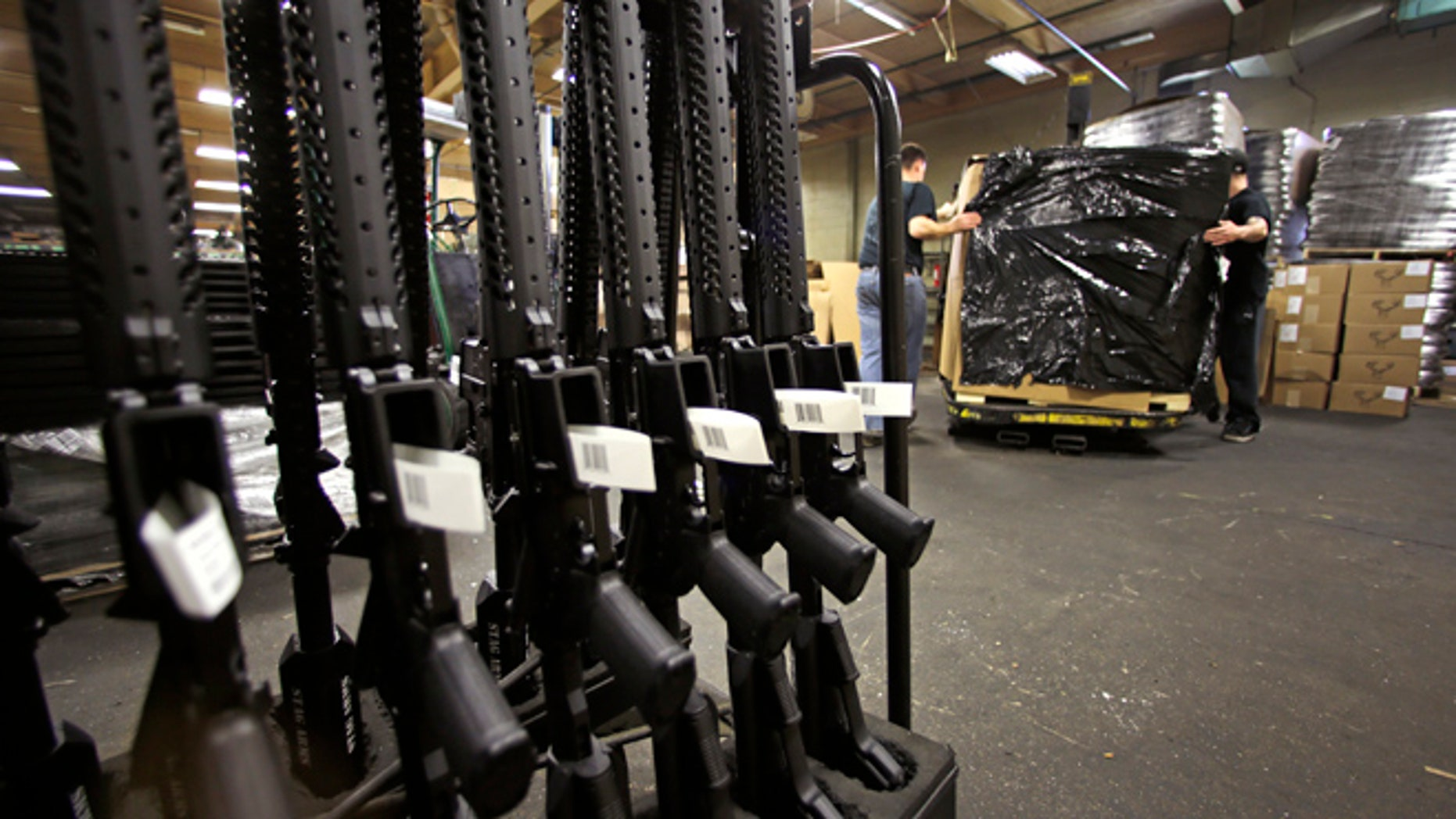 A rack of AR-15 rifles stand to be individually packaged as workers move a pallet of rifles for shipment at the Stag Arms company in New Britain, Conn., Wednesday, April 10, 2013.