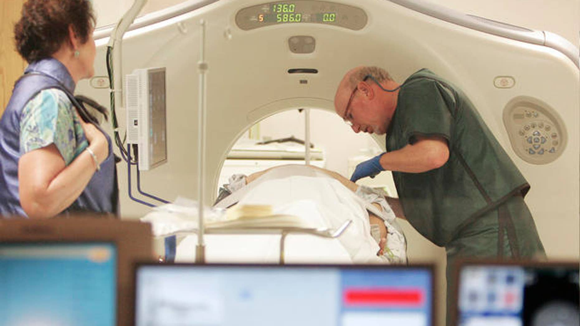 In this photo taken Thursday, June 3, 2010, Dr. Steven Birnbaum works a CT scanner with a patient at Southern New Hampshire Medical Center in Nashua, N.H. (AP Photo/Jim Cole)