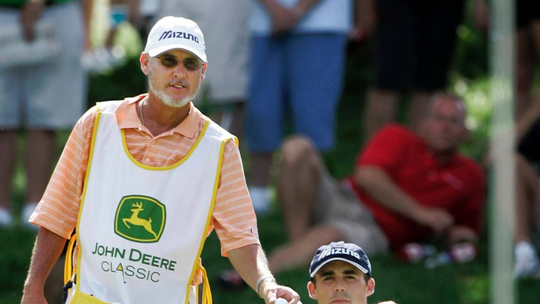 FILE - In this July 15, 2007, file photo, golfer Jonathan Byrd, right, shows caddie Mike Hicks the contour of the 17th green during John Deere Classic golf tournament at the TPC Deere Run golf course in Silvis, Ill. A group of PGA Tour caddies has filed a class-action lawsuit Tuesday, Feb. 3, 2015, in northern California, demanding that the tour compensate them for wearing bibs.  Hicks was named as the two class representatives. The other was Kenny Harms, who caddies for Kevin Na.   (AP Photo/Charles Rex Arbogast, File)