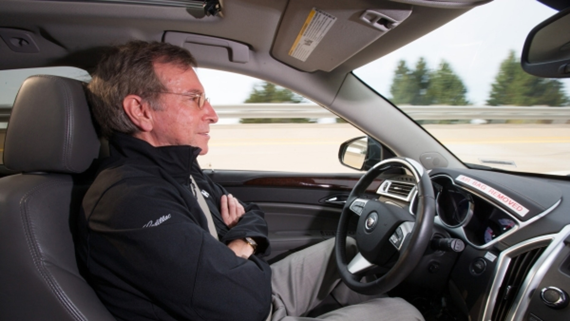 "General Motors Staff Researcher Dr. Jeremy Salinger road tests a Cadillac semi-autonomous driving technology it calls ""Super Cruise"" that is capable of fully automatic steering, braking and lane-centering in highway driving under certain optimal conditions Friday, March 23, 2012 in Milford, Michigan. Super Cruise is designed to ease the driver's workload on the freeway, in both bumper-to-bumper traffic and on long road trips by relying on a fusion of radar, ultrasonic sensors, cameras and GPS map data. The system could be ready for production vehicles by mid-decade. (Photo by John F. Martin for Cadillac)"