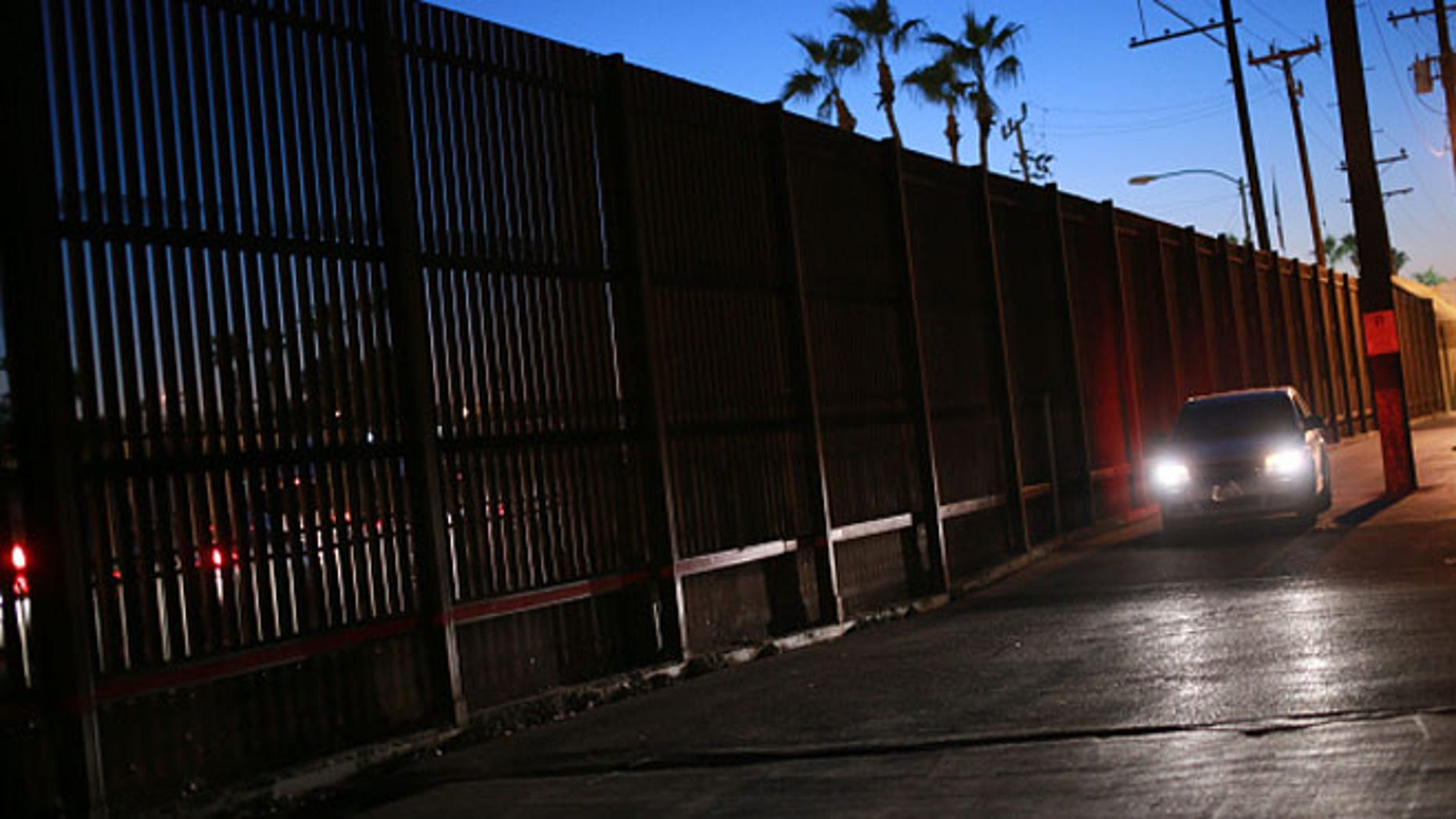 CALEXICO, CA - NOVEMBER 19:  A car drives along the U.S. - Mexico border wall on November 19, 2014 in Calexico, California. U.S. President Barack Obama plans to announce executive action on immigration reform Thursday Evening.  As many as five million undocumented immigrants could, on a temporary basis, be granted work permits and exempted from deporation. (Photo by Sandy Huffaker/Getty Images)