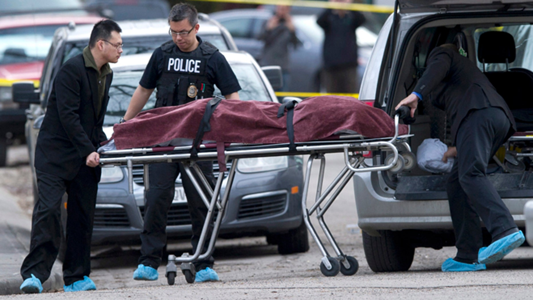 April 15, 2014: Police remove a body from the scene of a multiple fatal stabbing in northwest Calgary, Alberta.