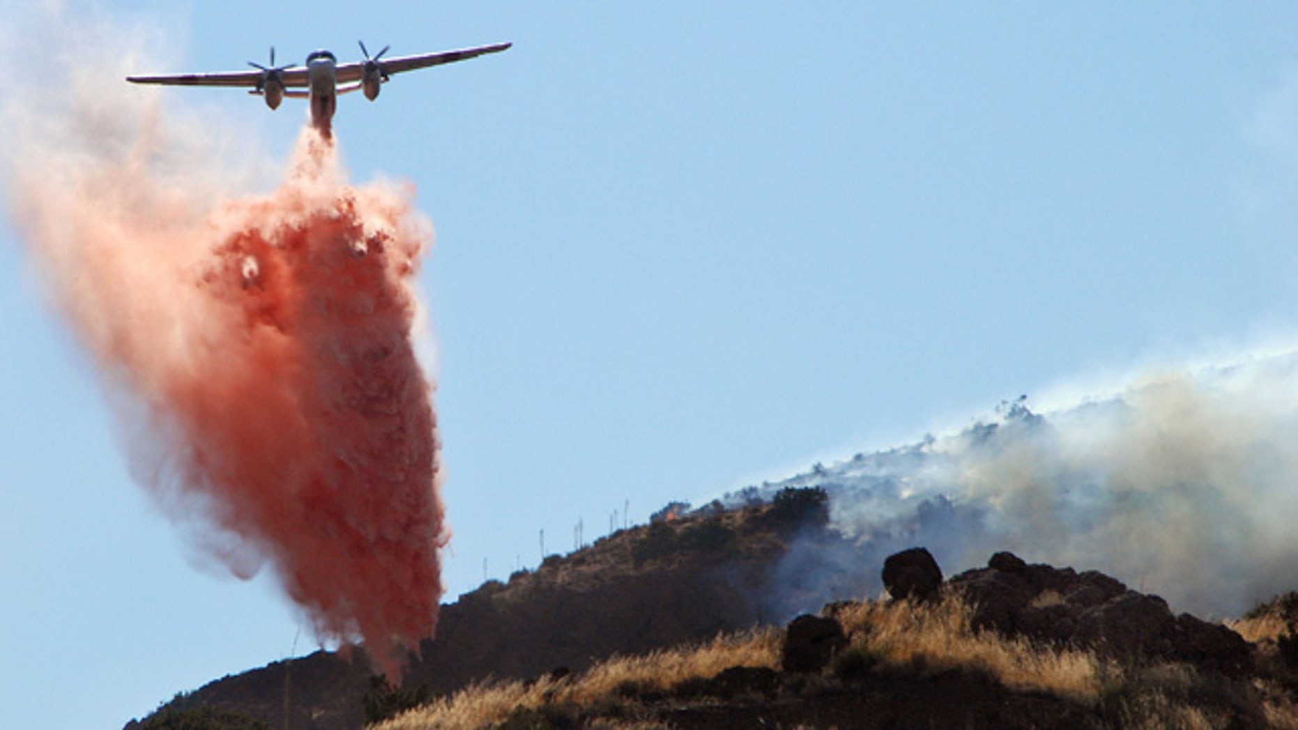Sept. 5: An air tanker drops retardant next to a flank of a wildfire in Agua Dulce, Calif.