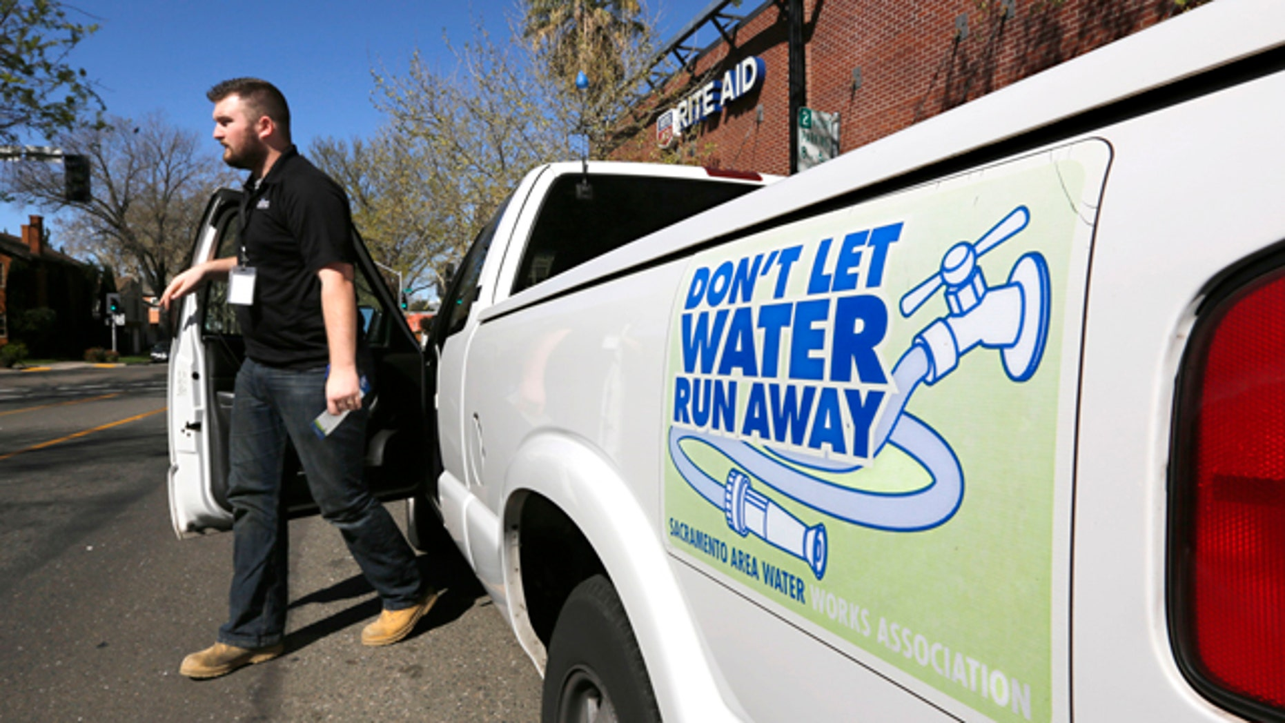 March 11, 2014: Steve Upton, an inspector for the water conservation unit for the Sacramento Utilities department, climbs out of his truck to make an inspection of an alleged water waste while making his rounds in Sacramento, Calif.  At least 45 water agencies throughout California have imposed mandatory restrictions on water use as their supplies run dangerously low. (AP Photo/Rich Pedroncelli)