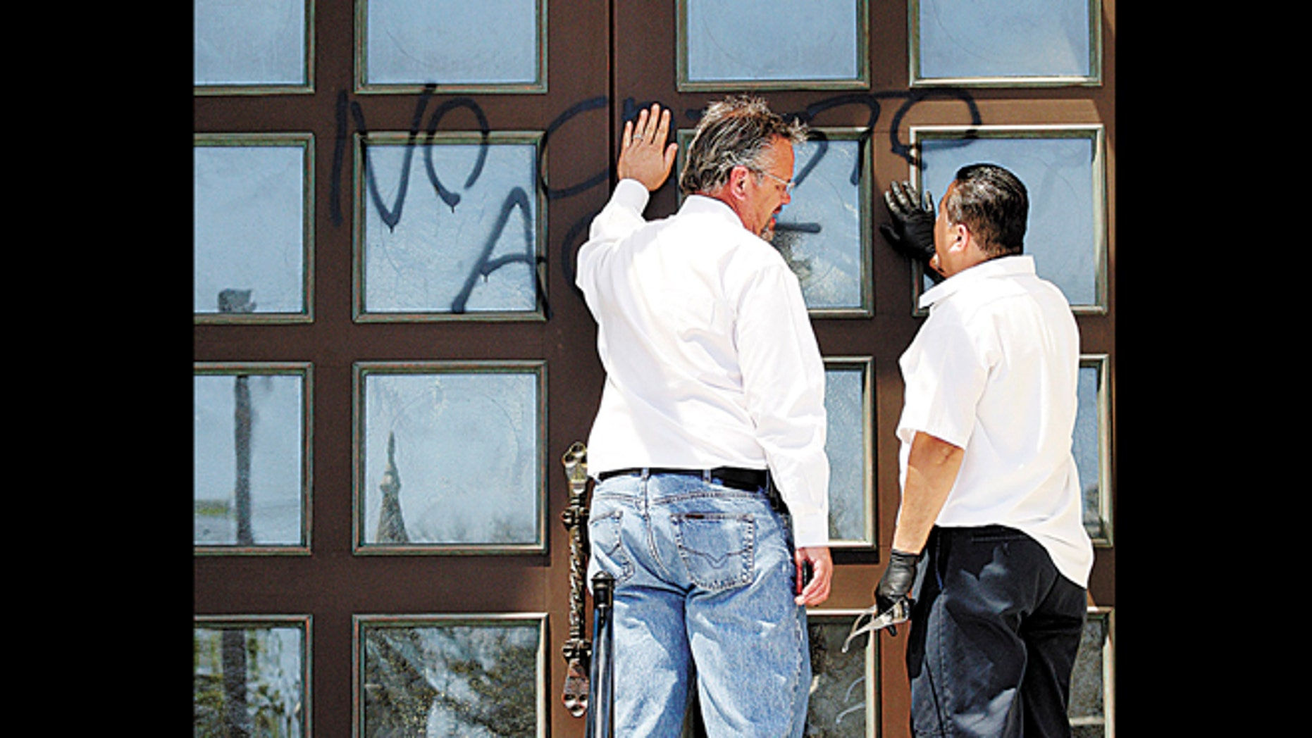 May 7, 2012: Church officials prepare to remove graffiti from Holy Cross Church in Santa Cruz, Calif.