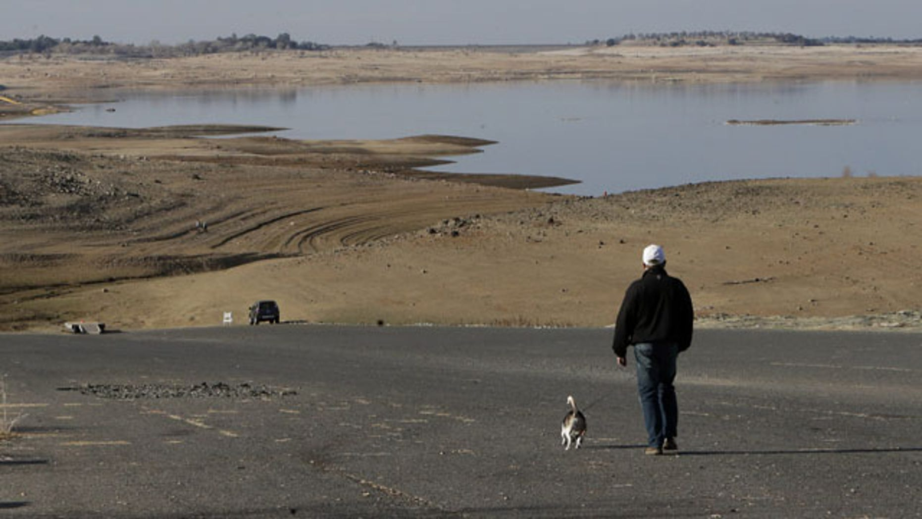 FILE -- In this Jan. 9, 2014 file photo a visitor to Folsom Lake, Calif., walks his dog down a boat ramp that is now several hundred yards away from the waters edge, in Folsom, Calif. Gov. Jerry Brown was governor the last time California had a drought of epic proportions, in 1975-76 and now is pushing a controversial $25 billion plan to build twin tunnels to ship water from the Sacramento-San Joaquin River Delta to farmland and cities further south. (AP Photo/Rich Pedroncelli,file)