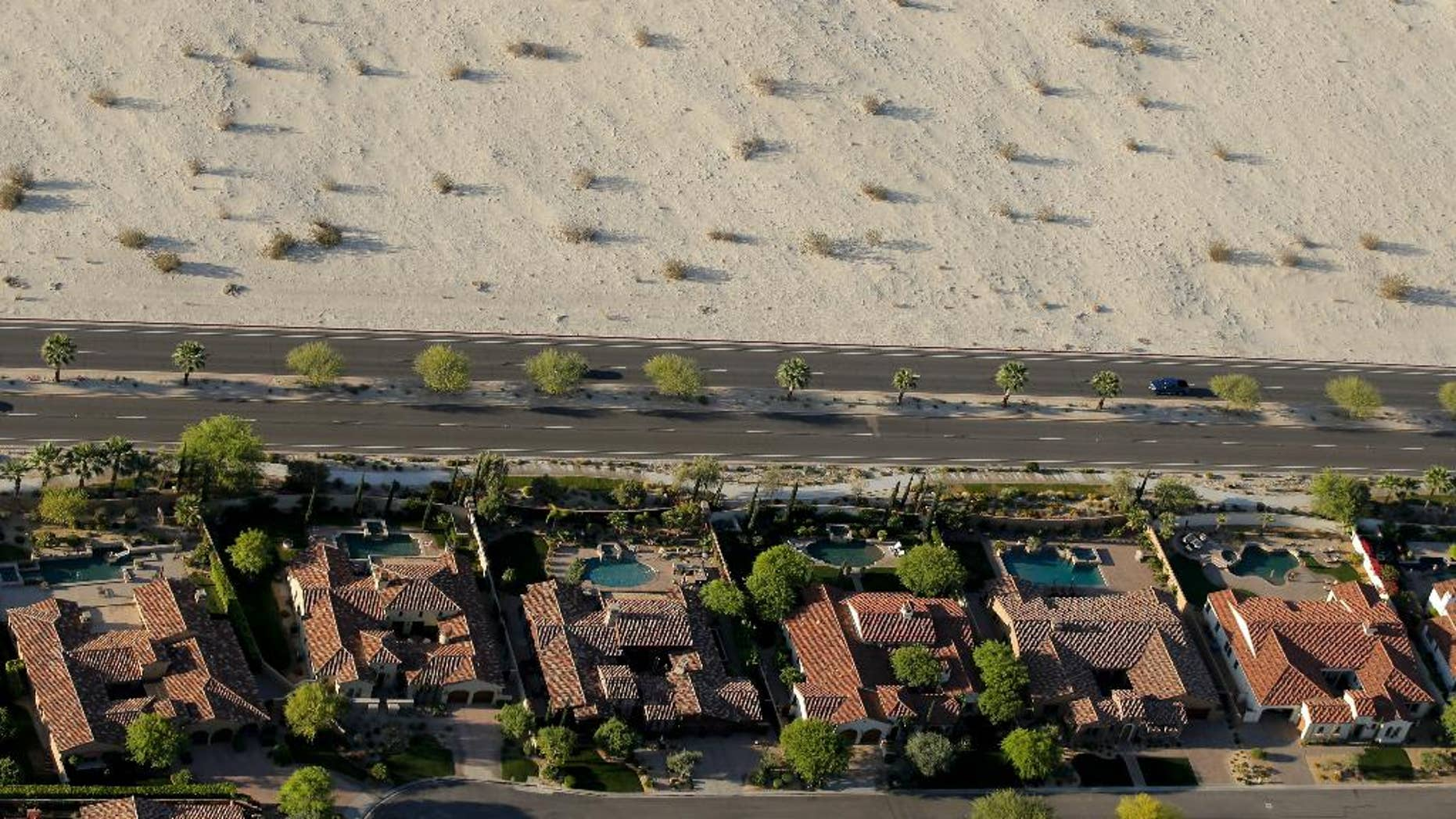 Homes with swimming pools border the desert of this neighborhood Friday, April 3, 2015, in Cathedral City, Calif. California Gov. Jerry Brown ordered officials Wednesday to impose statewide mandatory water restrictions for the first time in history as surveyors found the lowest snow level in the Sierra Nevada snowpack in 65 years of record-keeping. (AP Photo/Chris Carlson)