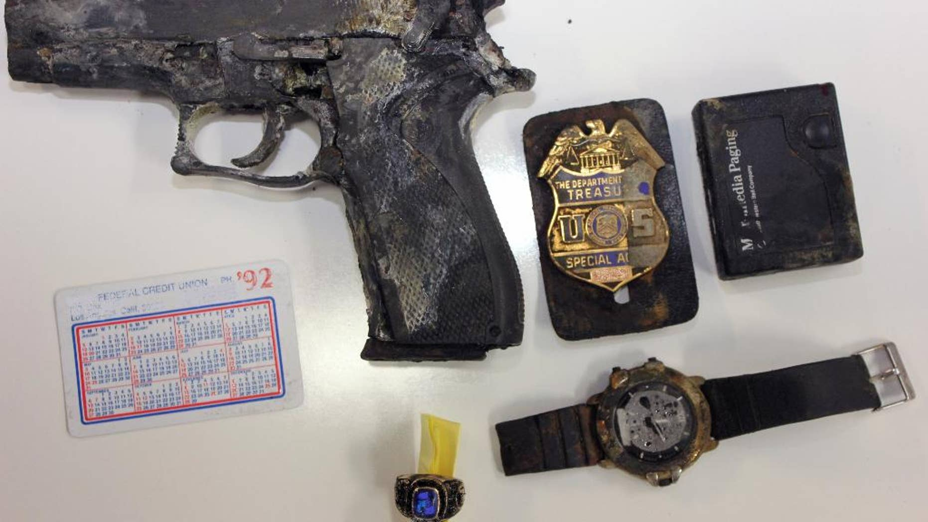 This undated photo provided by the Los Angeles County Sheriff's Department shows several items, including a handgun and badge of a federal agent, found in a backpack in shallow water by a man fishing at Castaic Lake in northern Los Angeles County. The agent said he got grief from his co-workers after his backpack went overboard during a 1992 boat trip, according to the Los Angeles Times. (AP Photo/ Los Angeles County Sheriff's Department)