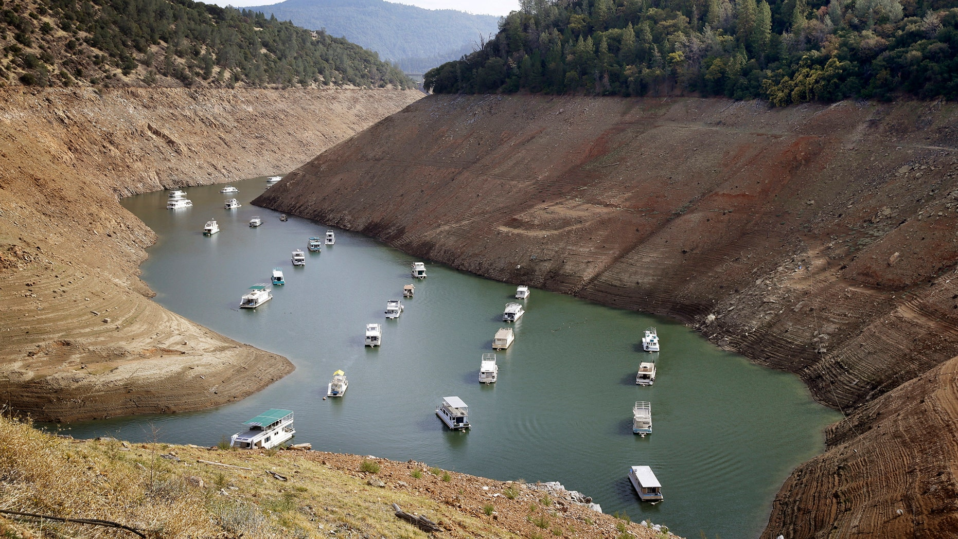 FILE - In this Thursday, Oct. 30, 2014, file photo, houseboats float in the drought-lowered waters of Oroville Lake near Oroville, Calif. Gov. Jerry Brown on Wednesday April 1, 2015 ordered sweeping and unprecedented measures to save water in California. Surveyors on Wednesday found the lowest snow level in the Sierra Nevada snowpack in 65 years of record-keeping, marking a fourth consecutive year of vanishing snow that California depends on to melt into rivers and replenish reservoirs.