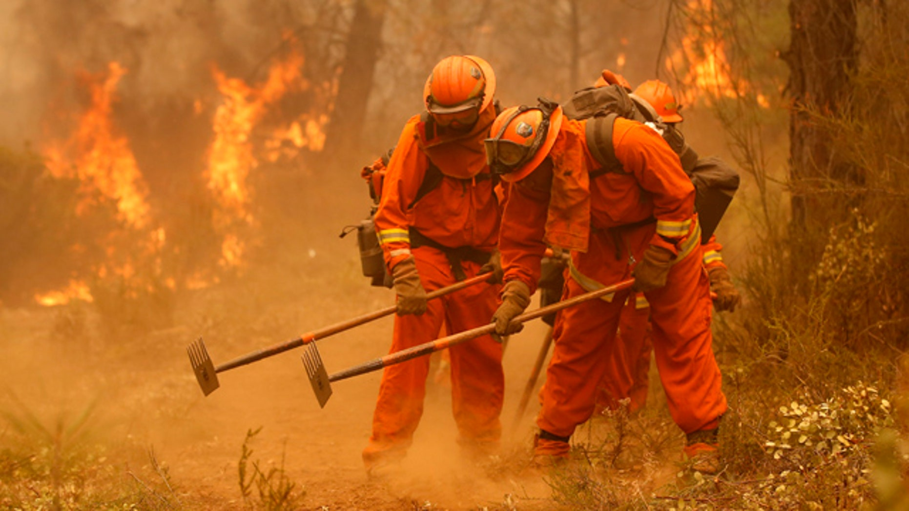 Sept. 12, 2015: A California Department of Corrections and Rehabilitation inmate work crew builds a containment line ahead of flames from a fire near Sheep Ranch, Calif. (AP Photo/Rich Pedroncelli, File)