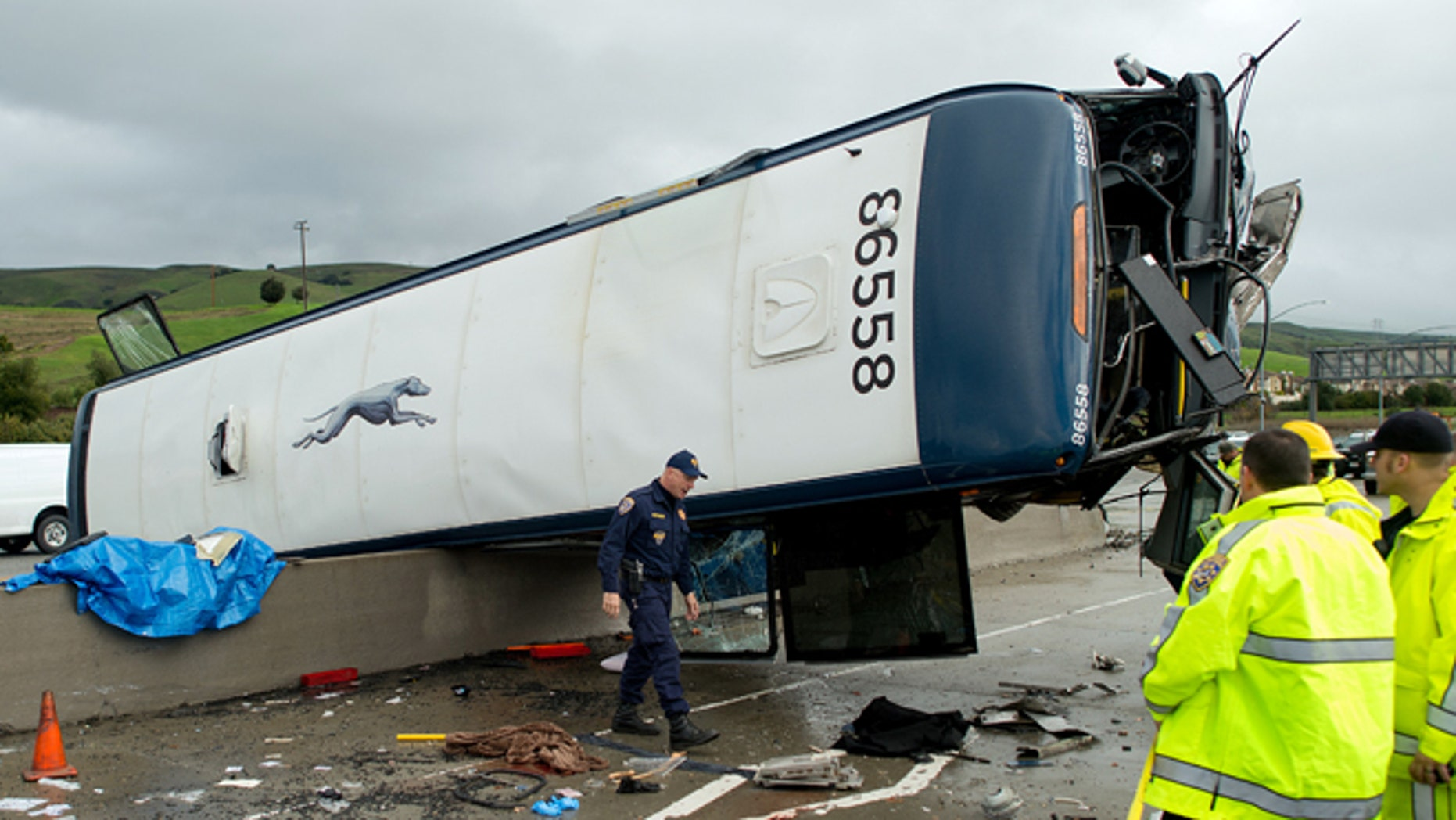 A California Highway Patrol investigator examines the scene of a fatal Greyhound bus crash, Tuesday, Jan. 19, 2016, in San Jose, Calif. The bus flipped on its side while traveling north on Highway 101, according to the San Jose Fire Department. (AP Photo/Noah Berger)