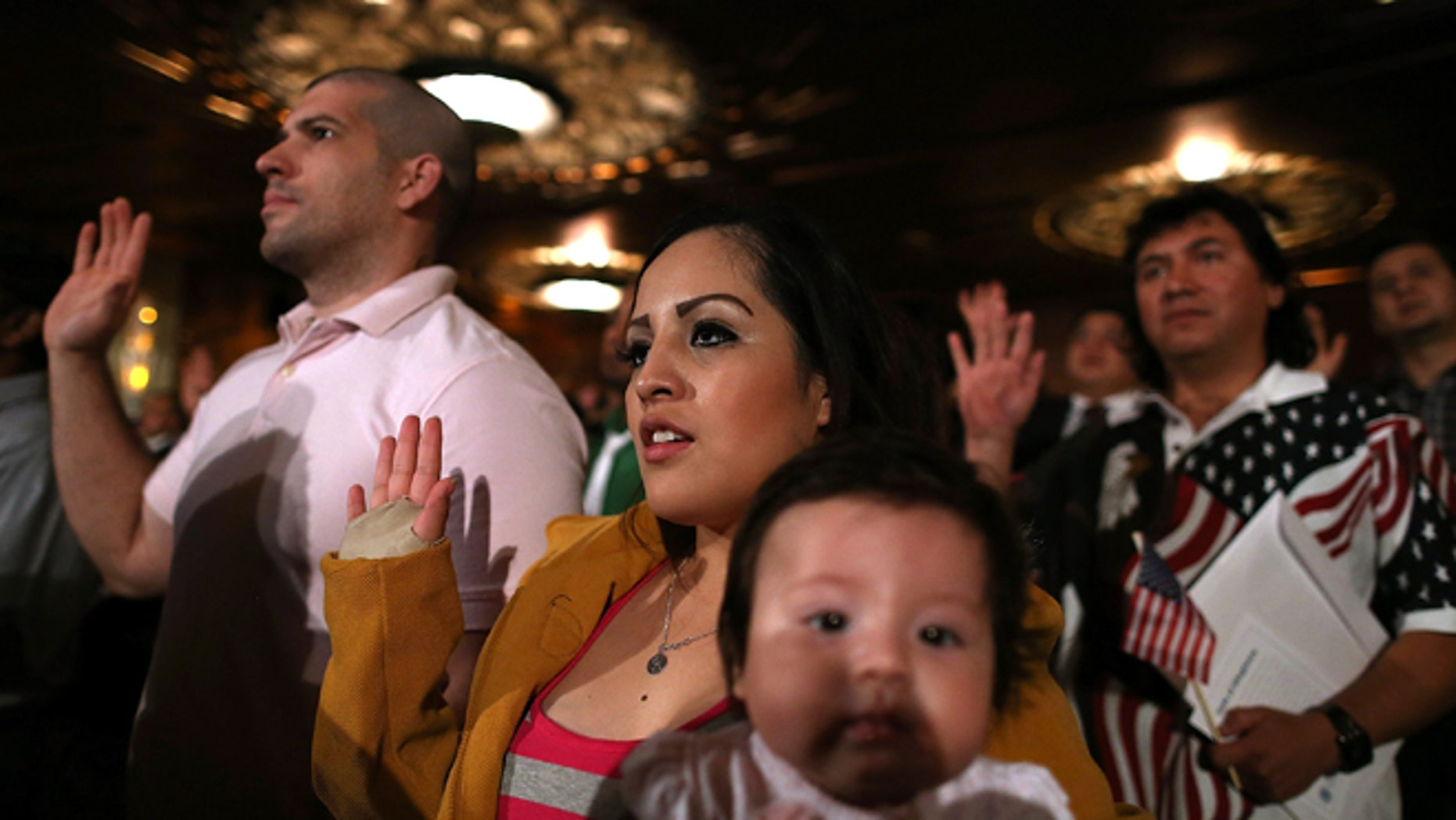 OAKLAND, CA - JULY 30:  Karen Franco of Peru holds her four-month old daughter Kyara Franco as she is sworn in as a U.S. citizen during a naturalization ceremony at the Paramount Theatre on July 30, 2013 in Oakland, California. Over 1,100 immigrants became U.S. citizens at the naturalization ceremony.  (Photo by Justin Sullivan/Getty Images)
