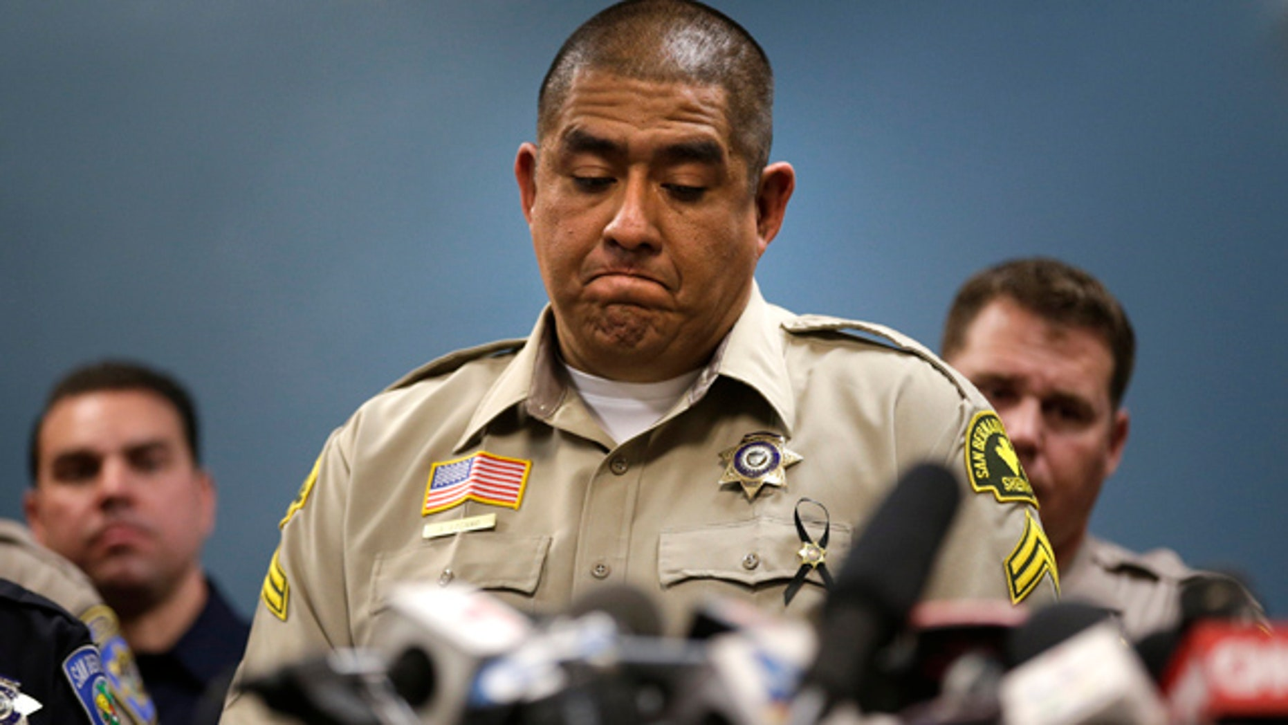 Dec. 8, 2015: San Bernardino County (Calif.) Sheriff's detective Jorge Lozano, center, pauses while answering questions during a news conference with the first responders on the scene of last week's fatal shooting at a social services center. (AP Photo/Jae C. Hong)