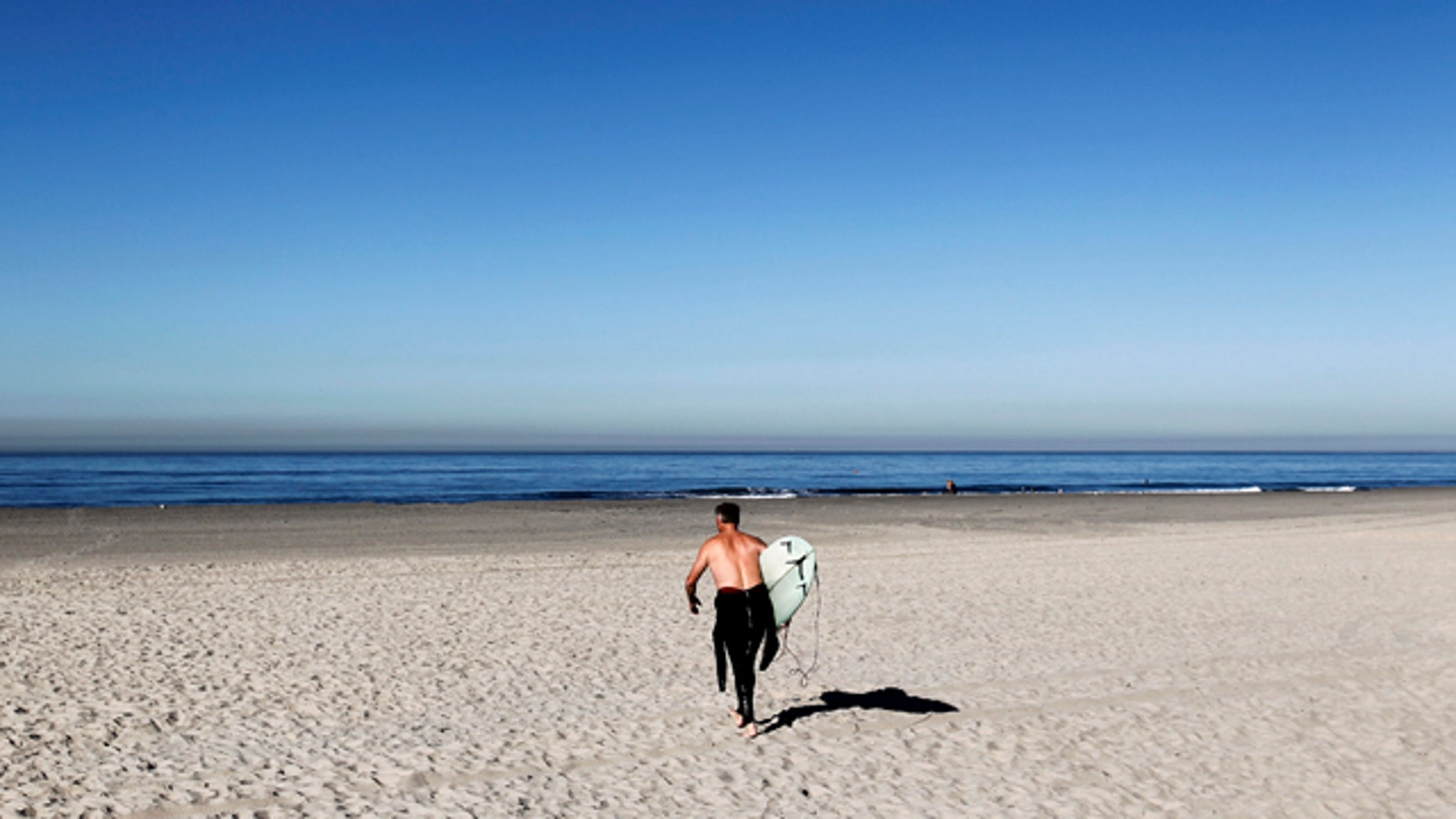 Dec. 13, 2010: A lone surfer walks out to ride waves at Pacific Beach during a warm weather spell in San Diego, Calif.