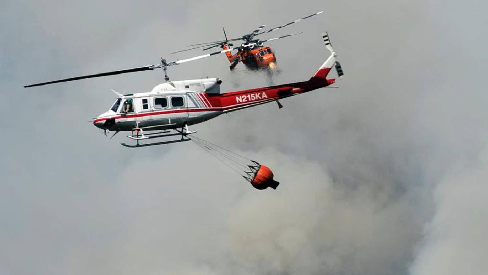A helicopter flies over Willow Creek Canyon as a wildfire continues burning in the Sierra near Bass Lake, Calif., Monday, July 27, 2015. More wildfires have torn across California so far this year compared with the same period of 2014, but firefighters said Monday that efforts to confine and extinguish the latest blazes have been more successful than in the past.  (Eric Paul Zamora/The Fresno Bee via AP)
