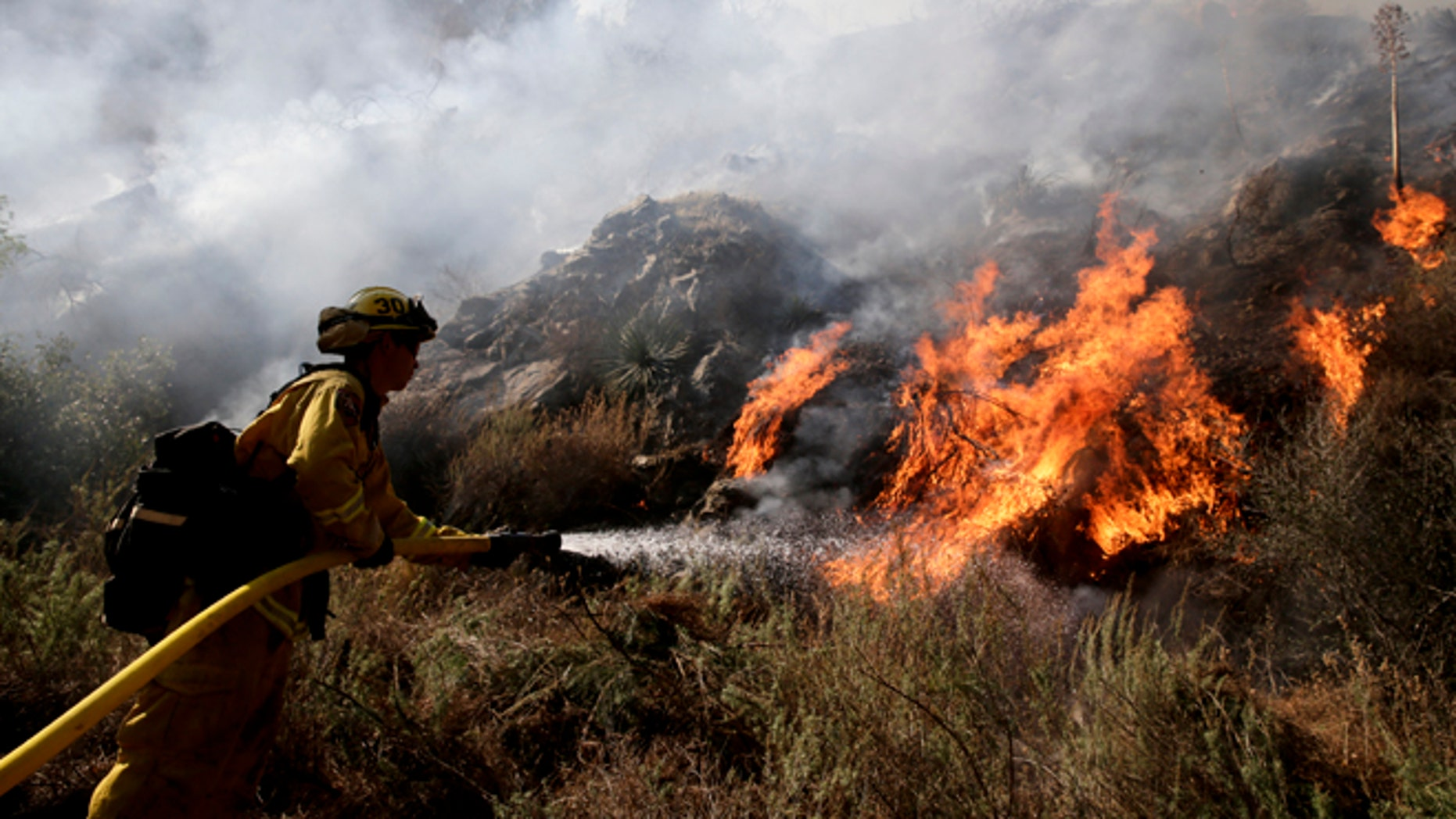 Firefighter Jeff Newby sprays water as he battles the Colby Fire on Friday, Jan. 17, 2014, near Azusa, Calif. Firefighters were chasing flare-ups Friday morning in a damaging wildfire that was largely tamed but kept thousands of people from their homes in the foothill suburbs northeast of Los Angeles.(AP Photo/Jae C. Hong)