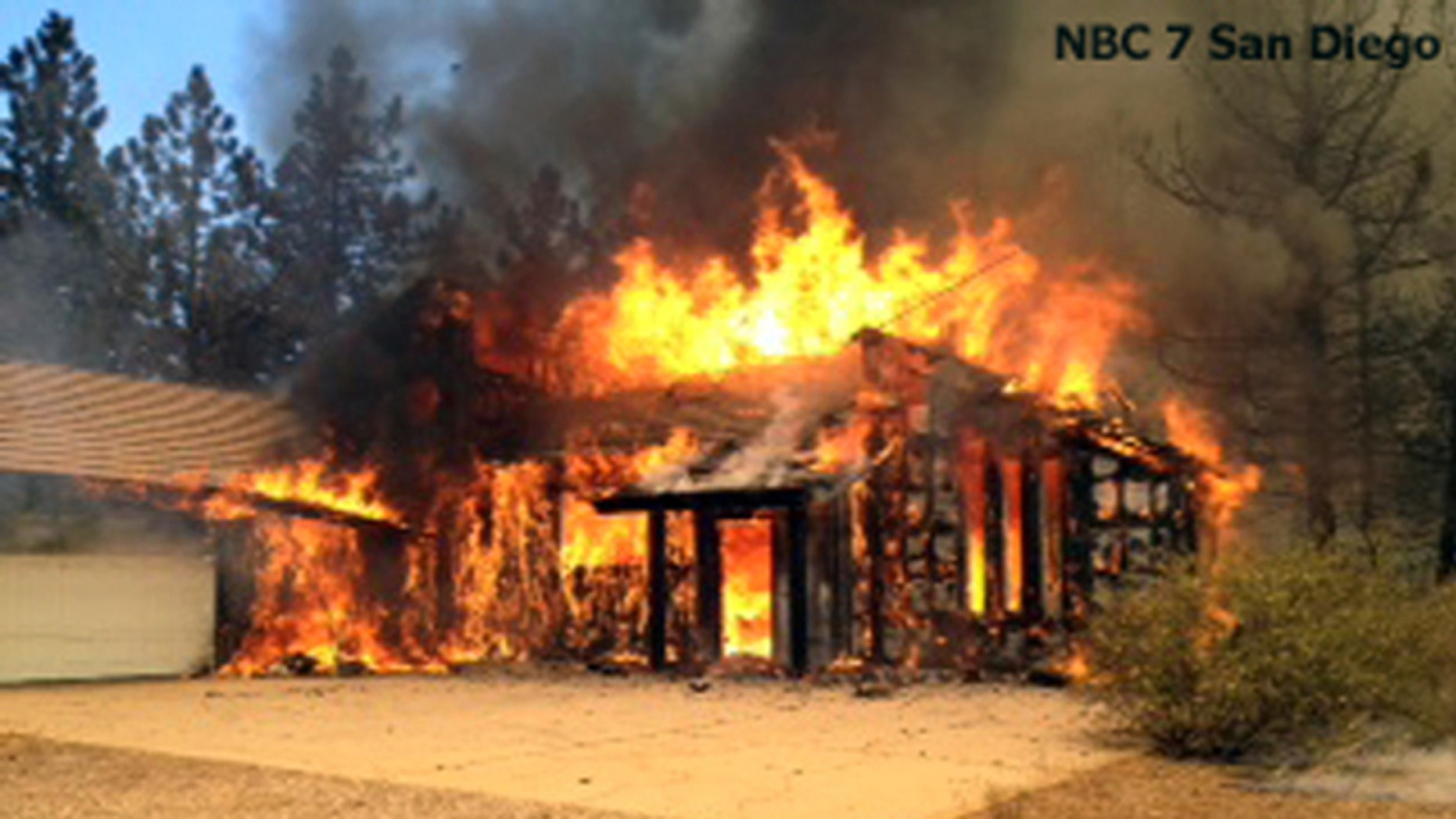 July 3, 2014: In this still frame from video provided by KNSD-TV, a home is fully involved in flames as crews scrambled to corral a wildfire that burned two homes near the San Diego County mountain town of Julian in Southern California. (AP/KNSD-TV)