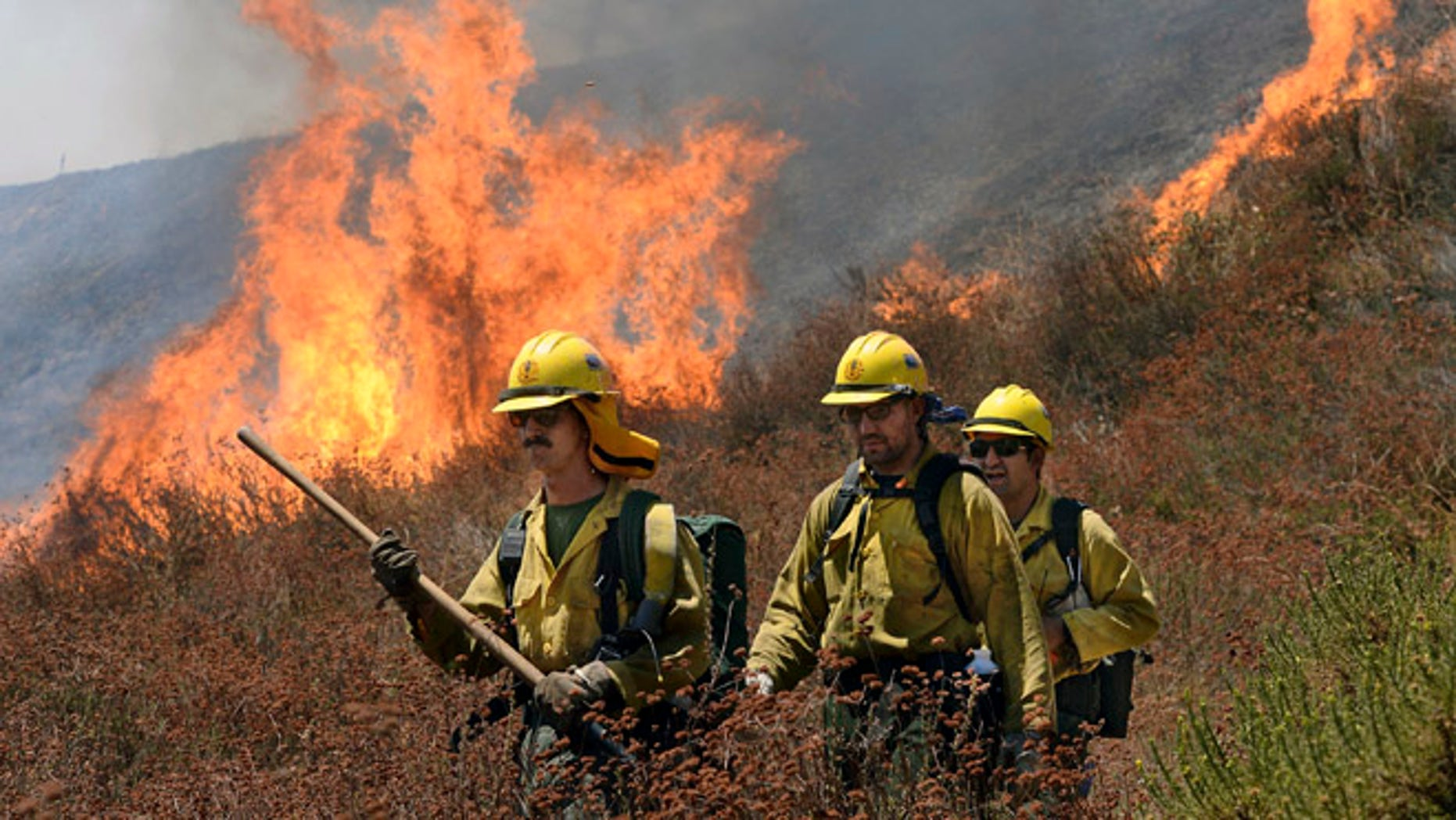 Firefighters battle the Bluecut Fire along Swarthout Canyon Road in the Cajon Pass, north of San Bernardino, Calif., Tuesday August 16, 2016. The blaze 60 miles east of Los Angeles has burned what appear to be several ranch outbuildings and forced evacuations in and around Lytle Creek. (Will Lester/The Sun via AP) MANDATORY CREDIT