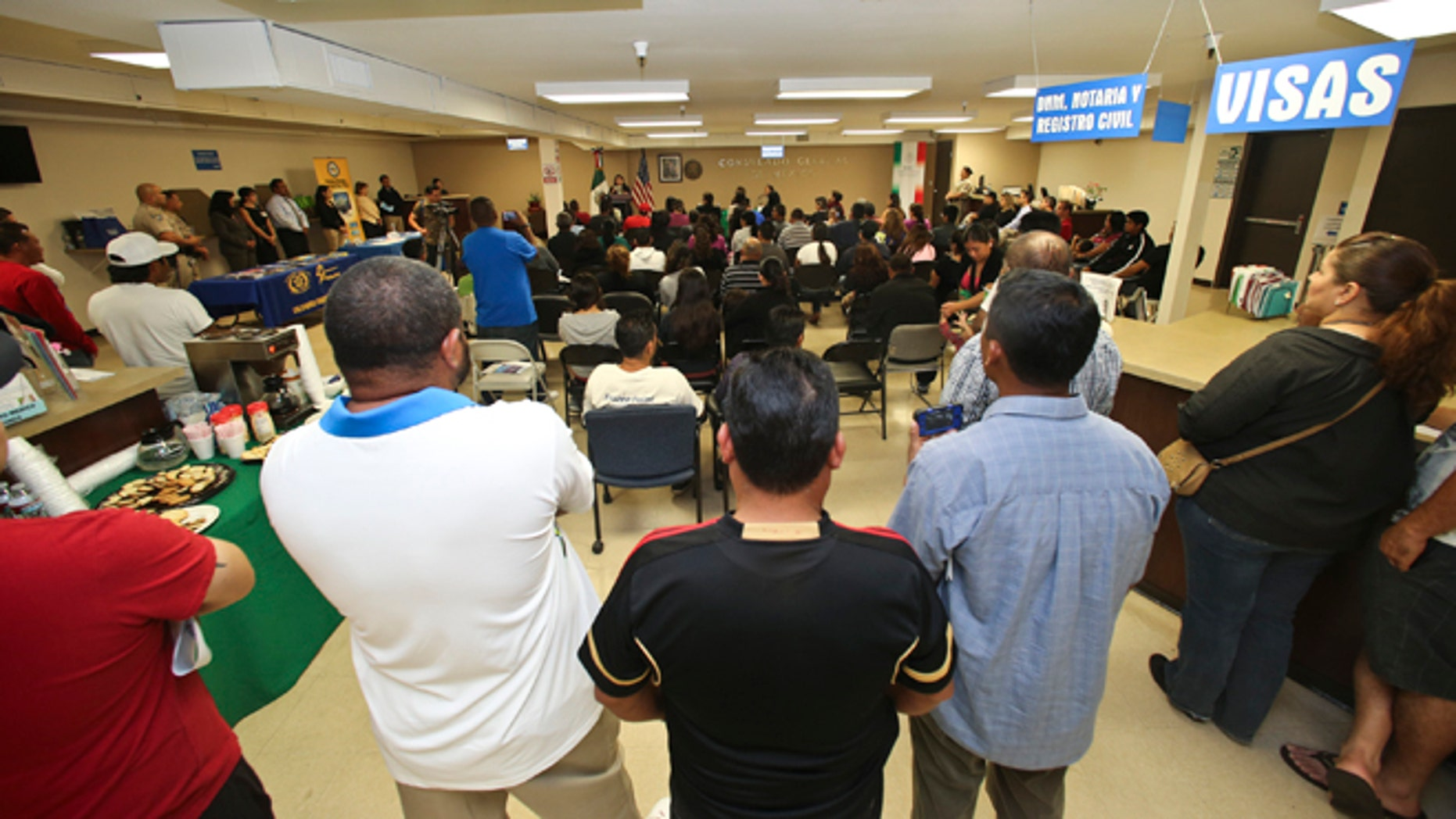 FILE - In this April 23, 2014, file photo, a crowd of approximately 80 immigrants fill a room as they listen to officials explain the process of getting a drivers license, during an information session at the Mexican Consulate, in San Diego. California is gearing up to start issuing driverâs licenses to immigrants in the country illegally in a bid to make the roads safer that could also give more than a million people access to state-issued identification. (AP Photo/Lenny Ignelzi,File)