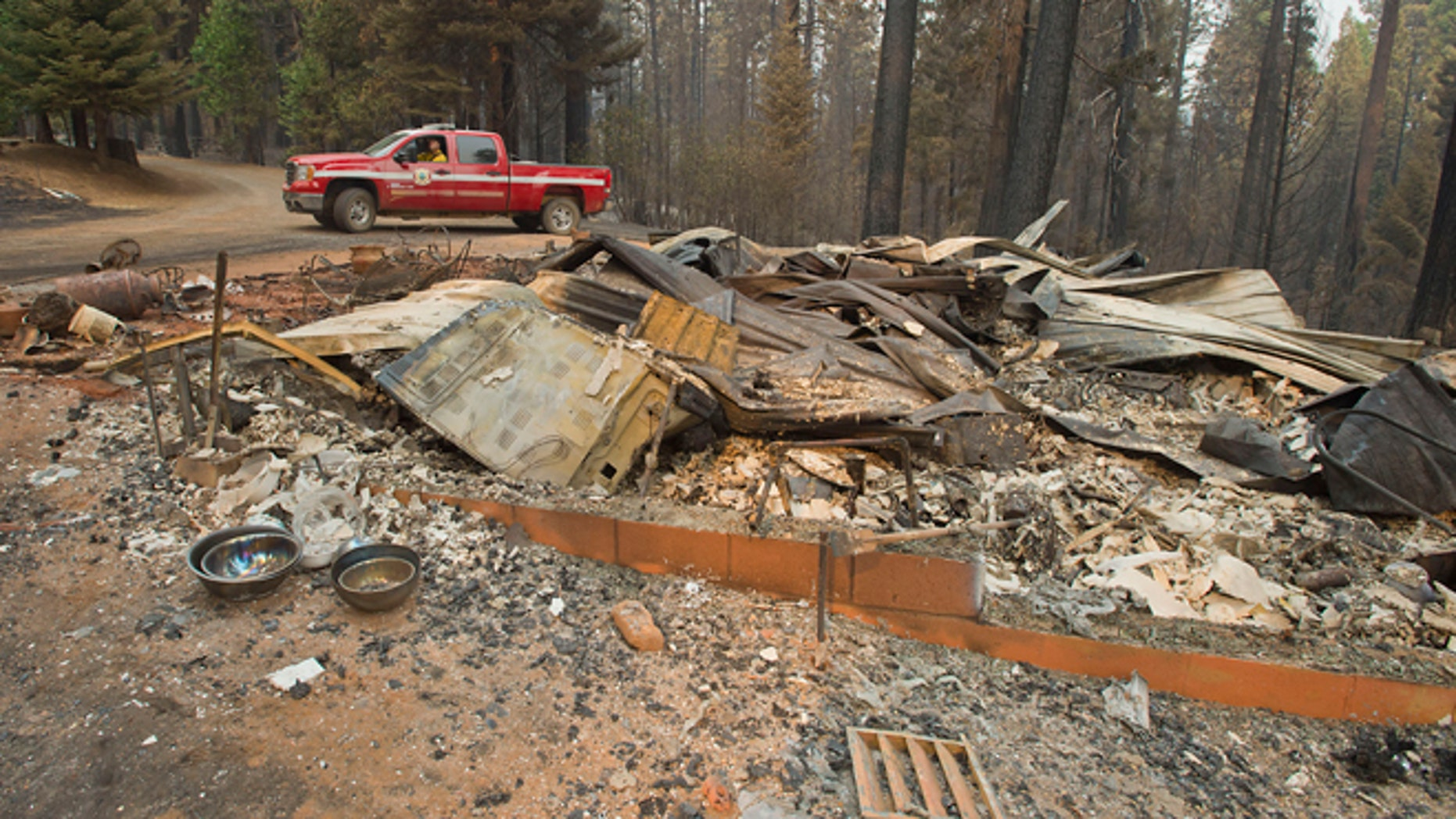 In a Friday, Sept. 19, 2014 file photo, a truck passes one of several homes that burned in the recent King fire near Icehouse in El Dorado County, Calif. Officials said Sunday, Sept. 21, 2014, that nearly three-dozen structures were destroyed in the massive Northern California wildfire that continues to spread more than a week after it started.