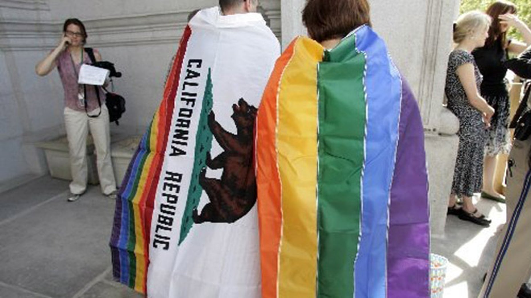 Gay rights supporters wear a California state flag, left, and a gay pride flag outside of the California State Supreme Court building in San Francisco.