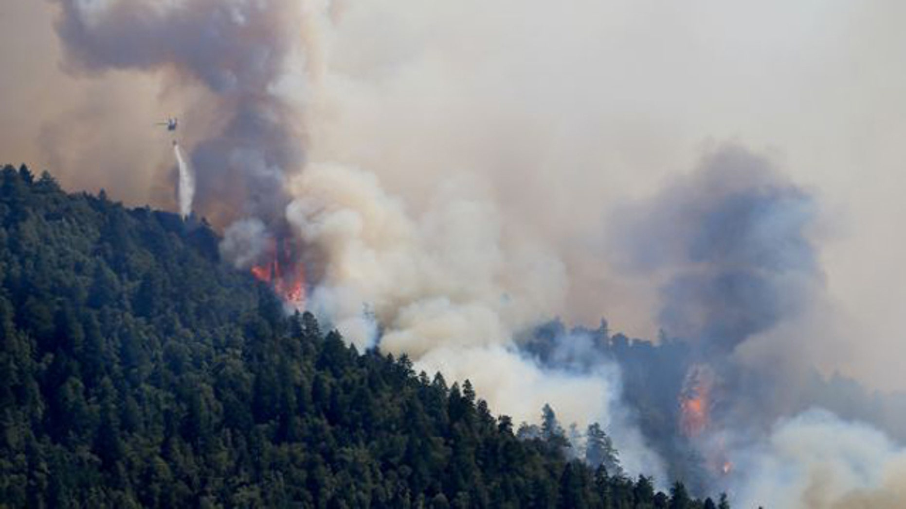 August 8, 2014: An Air National Guard helicopter makes a water drop as the Lodge Fire between Legget tand Laytonville, Calif., jumps the Eel River and moves upslope. (AP/Kent Porter)