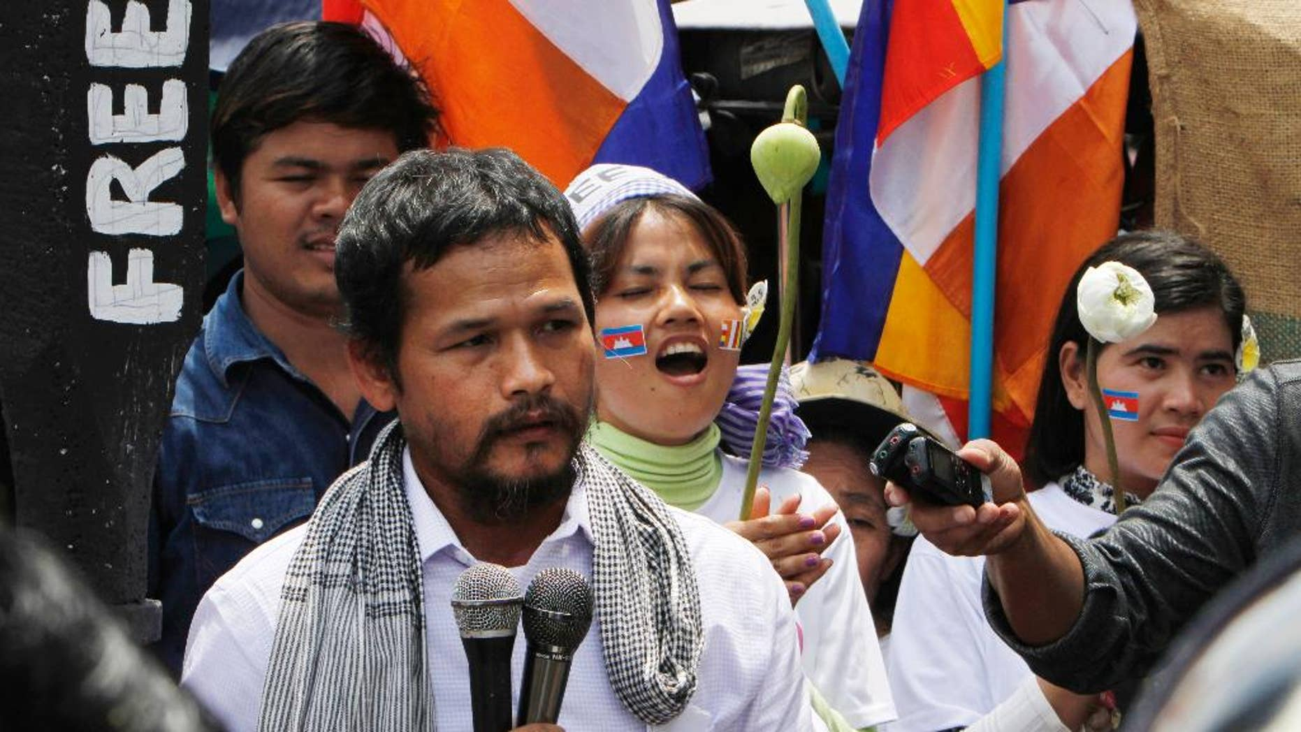 In this May 20, 2014, photo, Meach Sovannara of the opposition Cambodia National Rescue Party gives a speech at a blocked main street near the Phnom Penh Municipality Court during a gathering to call for the release of anti-government protesters who were arrested in a police crackdown, in Phnom Penh, Cambodia. A court on Tuesday, July 21, 2015, sentenced 11 members of the opposition party to long prison terms after convicting them of insurrection in connection with a violent protest in 2014. Meach Sovannara, an opposition spokesman, was one of three defendants sentenced to 20 years in prison for leading the violent protest. Eight others received seven-year sentences for taking part. (AP Photo/Heng Sinith)