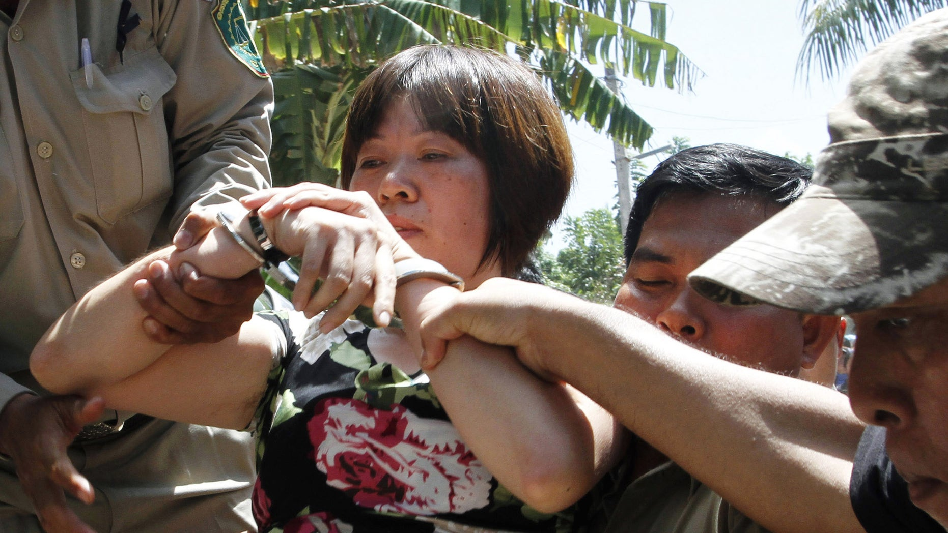 Oct. 22, 2012: In this photo, Wang Zia Chao, 43, a Chinese factory supervisor, is escorted by Cambodian police officers after being detained, on the outskirts of Phnom Penh, Cambodia.